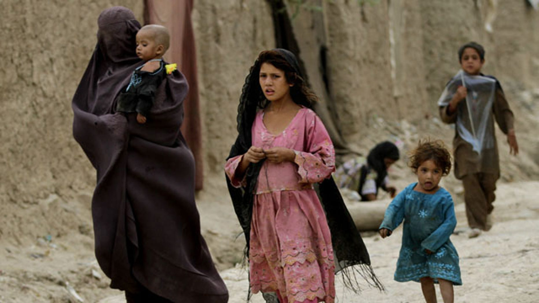 July 30, 2013: Displaced Afghans walks near their temporary homes on the outskirts of Kabul, Afghanistan. (AP Photo/Ahmad Jamshid)
