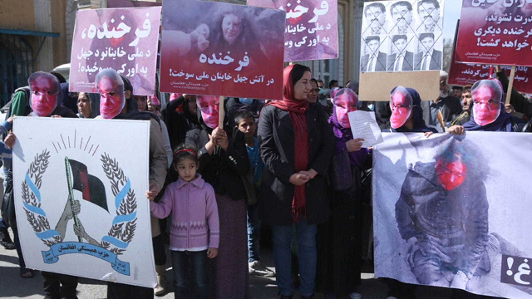 March 23, 2015: Young women wear masks and hold graphic pictures of  a 27 year-old woman, Farkhunda, who was beaten to death by a mob, during a protest by the Solidarity Party of Afghanistan at the site of the attack in Kabul. (AP Photo/Massoud Hossaini)