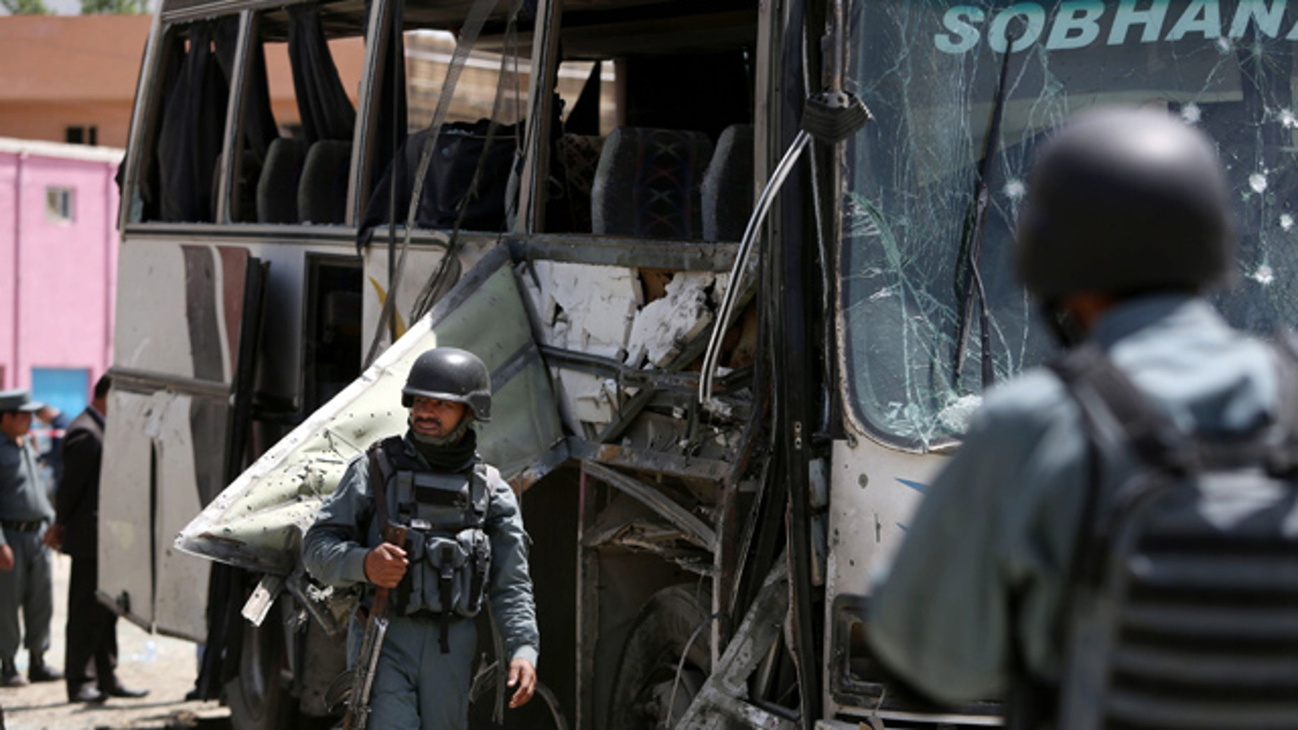 May 4, 2015: Afghan security forces inspect the site of a suicide attack in Kabul. An Afghan official says a suicide bomber struck a minibus carrying government employees in Kabul, killing at least one person and wounding more than a dozen. (AP Photo/Rahmat Gul)