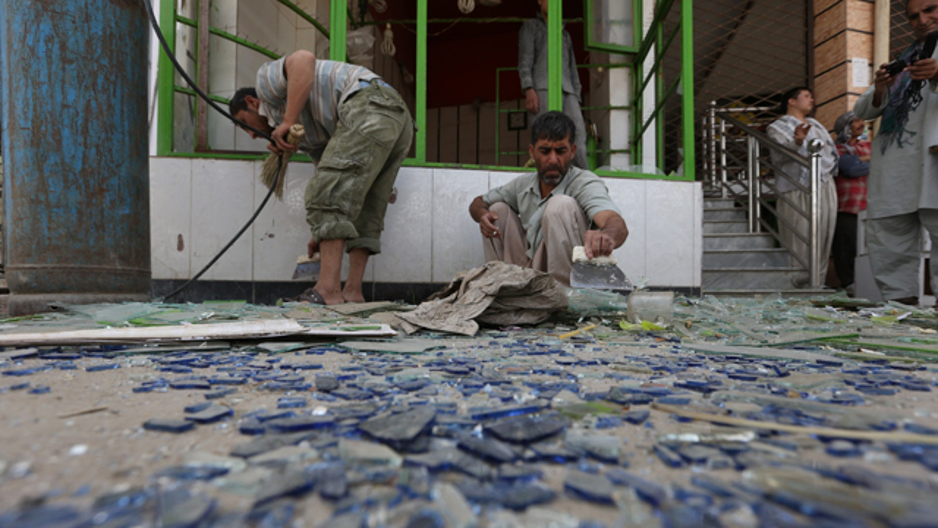 August 10, 2014: Afghan shopkeepers clean up broken glasses near the site of a suicide attack in Kabul, Afghanistan. (AP Photo/Rahmat Gul)