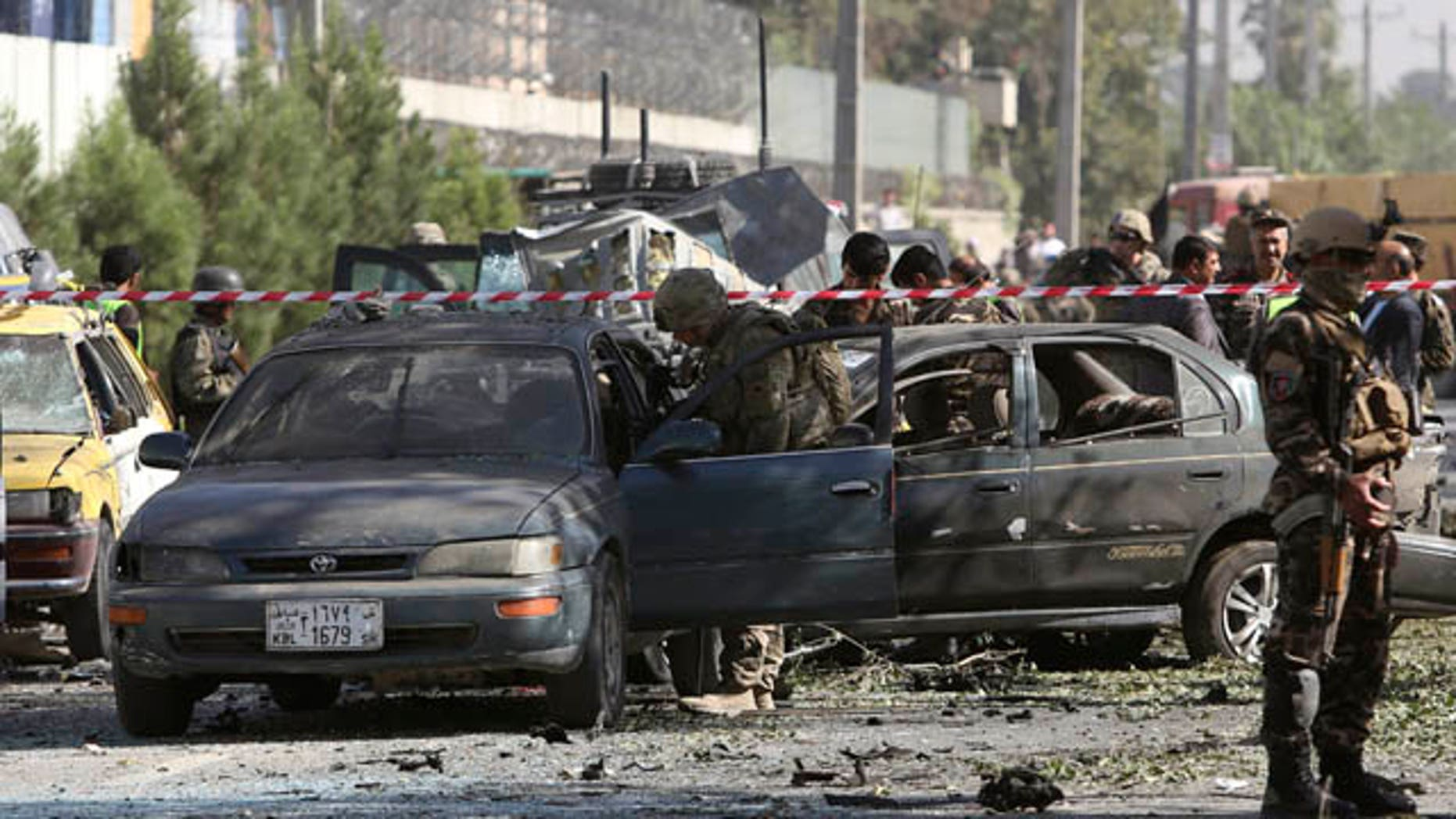 September 16, 2014: NATO and Afghan security forces inspect the site of a suicide attack in Kabul. (AP Photo/Rahmat Gul)