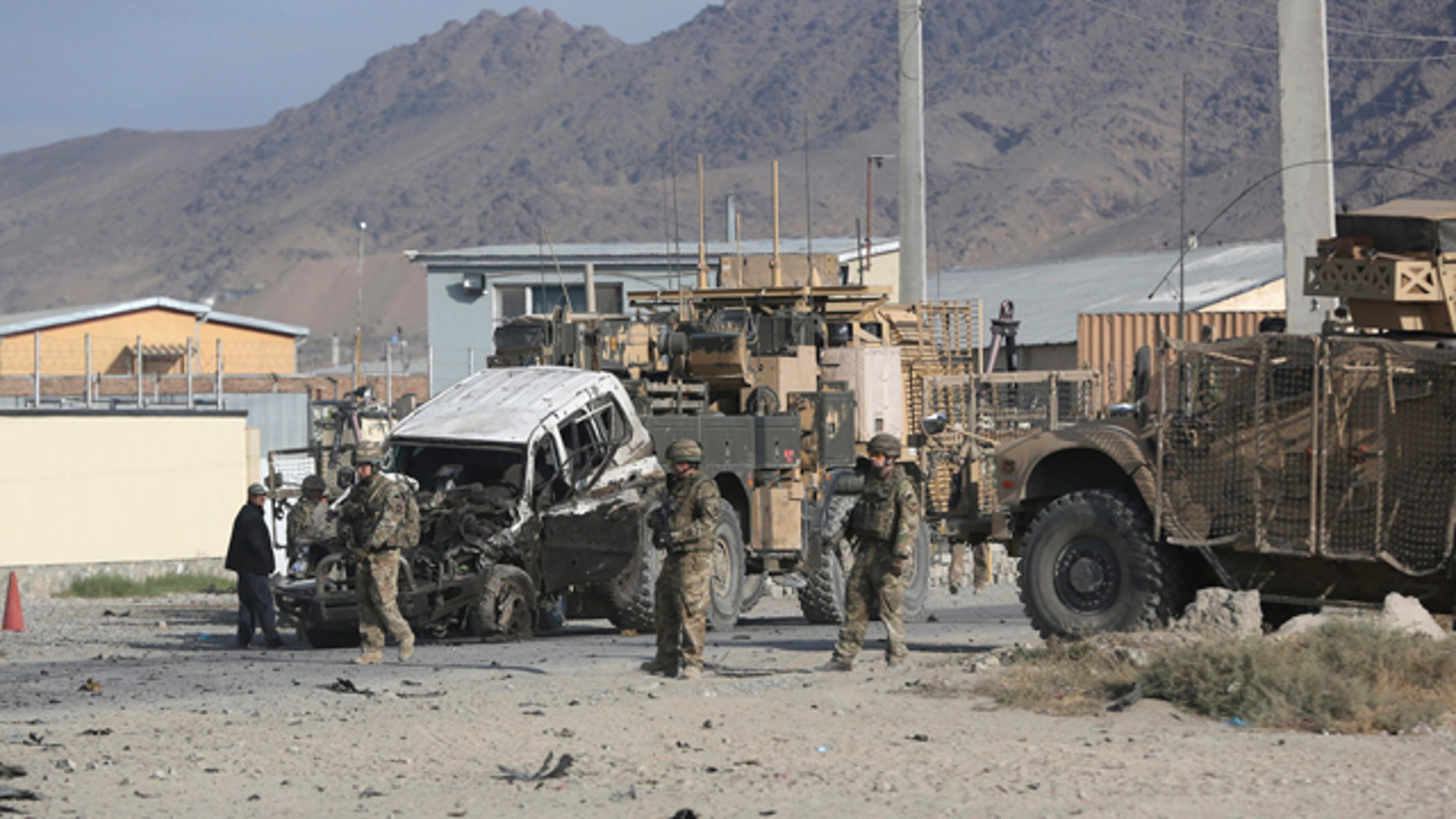 October 13, 2014: U.S. soldiers remove a destroyed vehicle from the site of a suicide attack in Kabul, Afghanistan. (AP Photo/Massoud Hossaini)