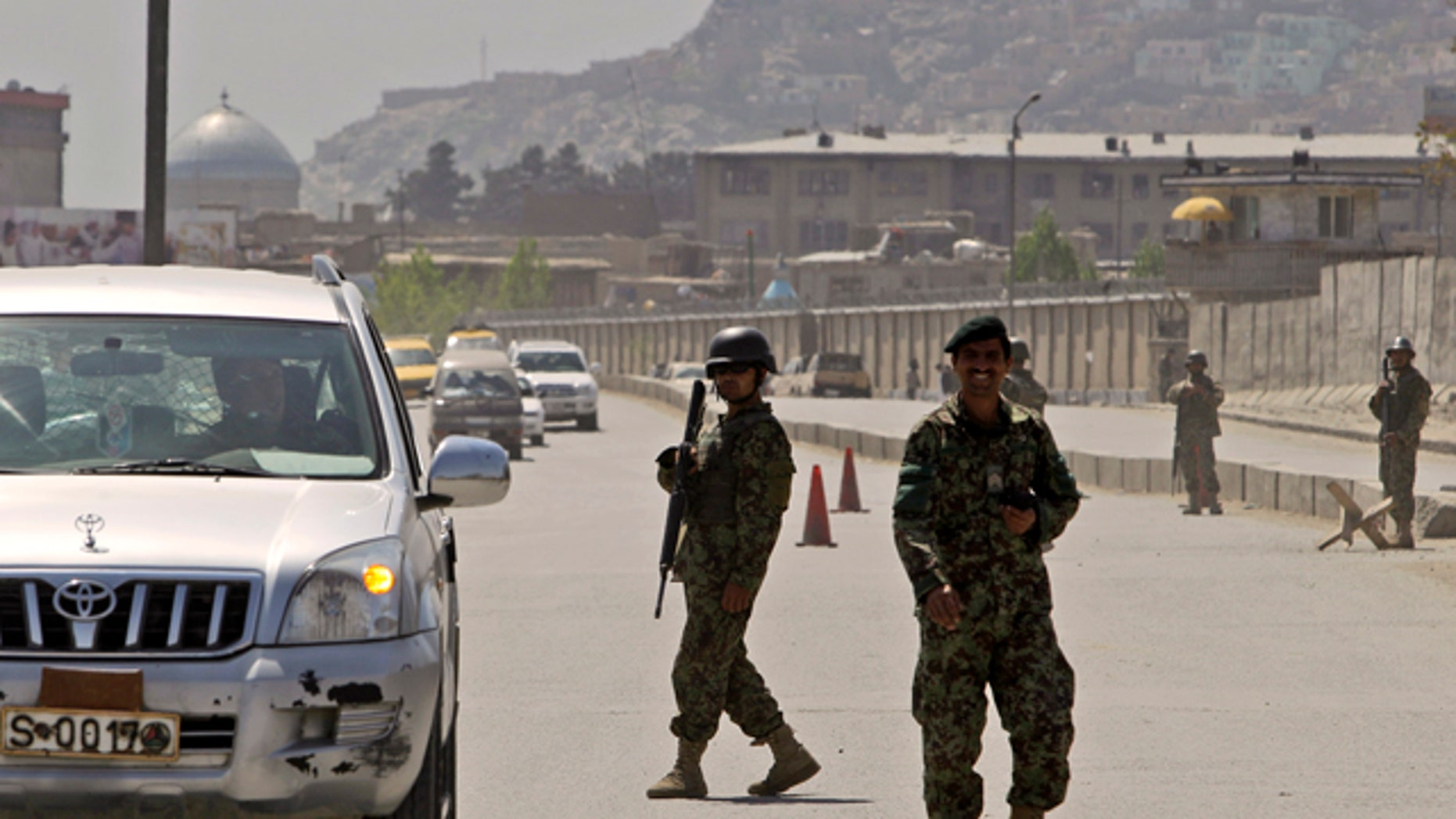 April 18: Afghan security officers secure the road near the Defense Ministry in Kabul, Afghanistan.
