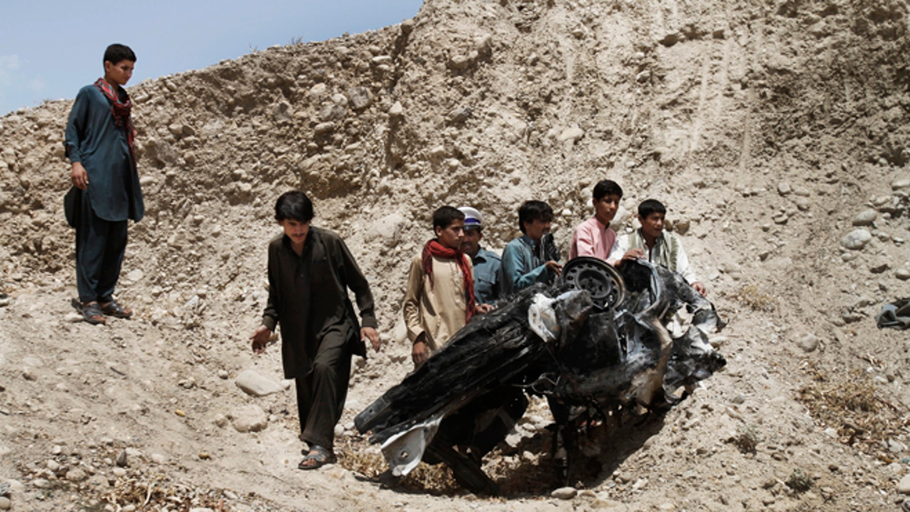 Aug. 12, 2012: Afghans push parts of a damaged vehicle off a hill after a roadside explosion on the outskirts of Laghman province east of Kabul, Afghanistan.