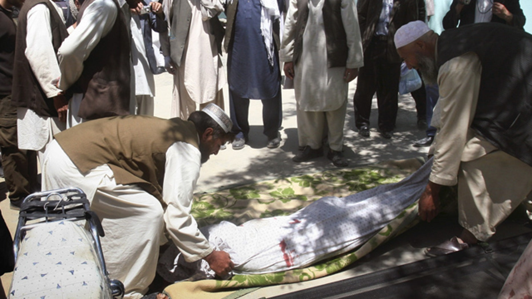 May 1, 2011: Relatives wrap the  body of a  civilian who was killed during a clash of militants with policemen in Ghazni southwest of Kabul, Afghanistan.
