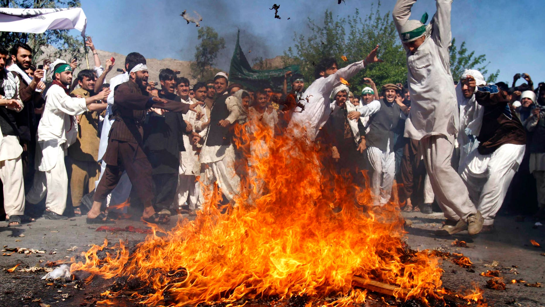 April 3: An Afghan protestor beats a burning effigy of U.S. President Barack Obama during a rally in Jalalabad, Afghanistan. Afghan protests against the burning of a Quran in Florida entered a third day with a demonstration in the major eastern city Sunday, while the Taliban called on people to rise up, blaming government forces for any violence. (AP)