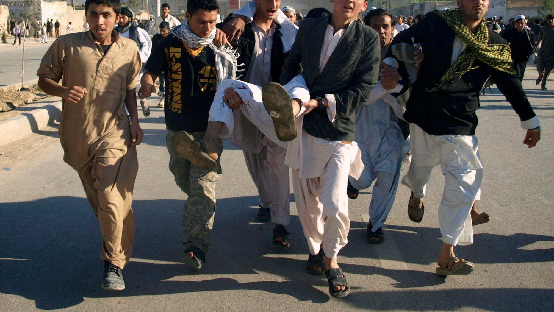 Afghans carrying a man, who got wounded following an attack on UN's office during a demonstration to condemn the burning of a copy of the Muslim holy book by a Florida pastor, in Mazar-i- Sharif north of Kabul, Afghanistan on Friday, April. 1, 2011. An Afghan official says seven people have been killed at a U.N. office in the northern city of Mazar-i-Sharif when a Koran burning protest turned violent.