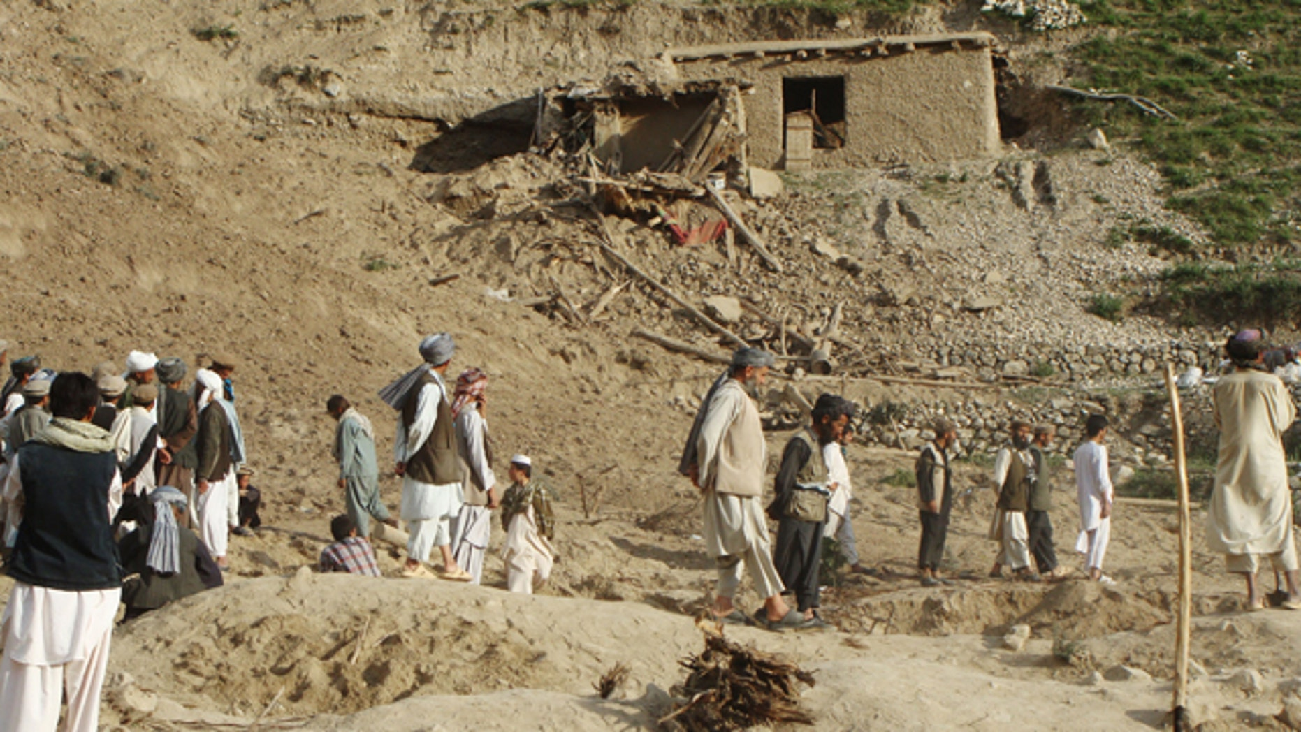 June 11, 2012: Afghans stand at the site after an earthquake hit Baghlan province, north of Kabul, Afghanistan.
