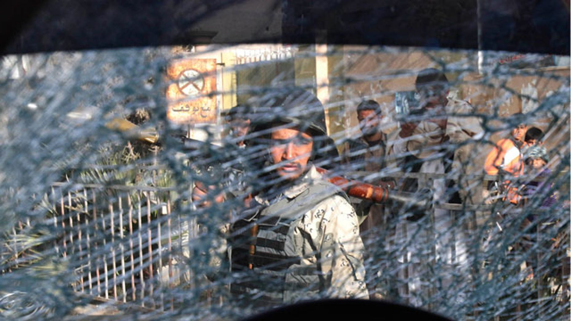 Mar. 6, 2012: An Afghan soldier passes by a chattered window of a destroyed police car after an explosive device went off in the center of Jalalabad, east of Kabul, Afghanistan.