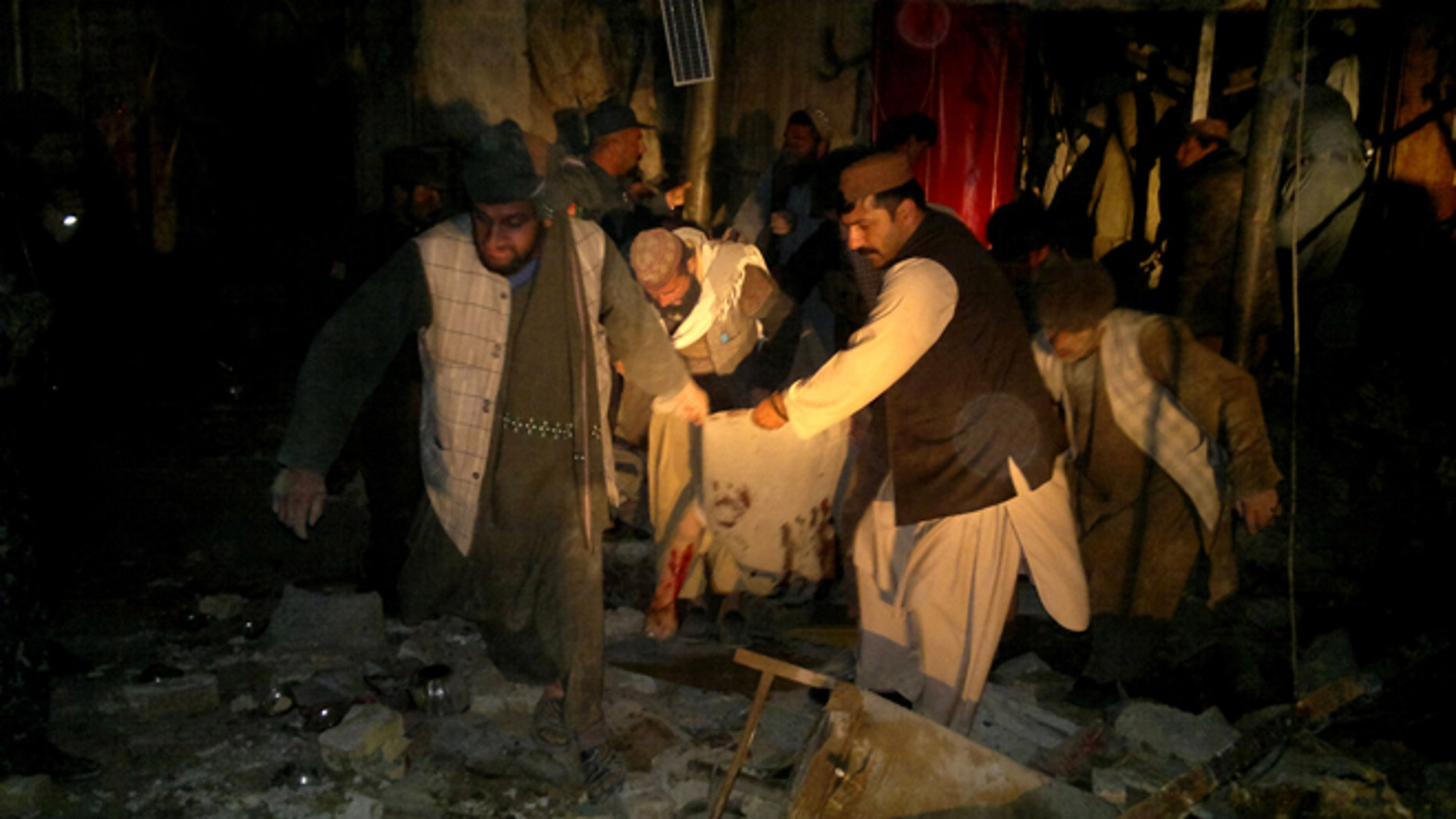 Feb. 25, 2014: Afghans carry the dead body of a civilian after a suicide attack in Trin Kot, capital of Uruzgan province,  Afghanistan.