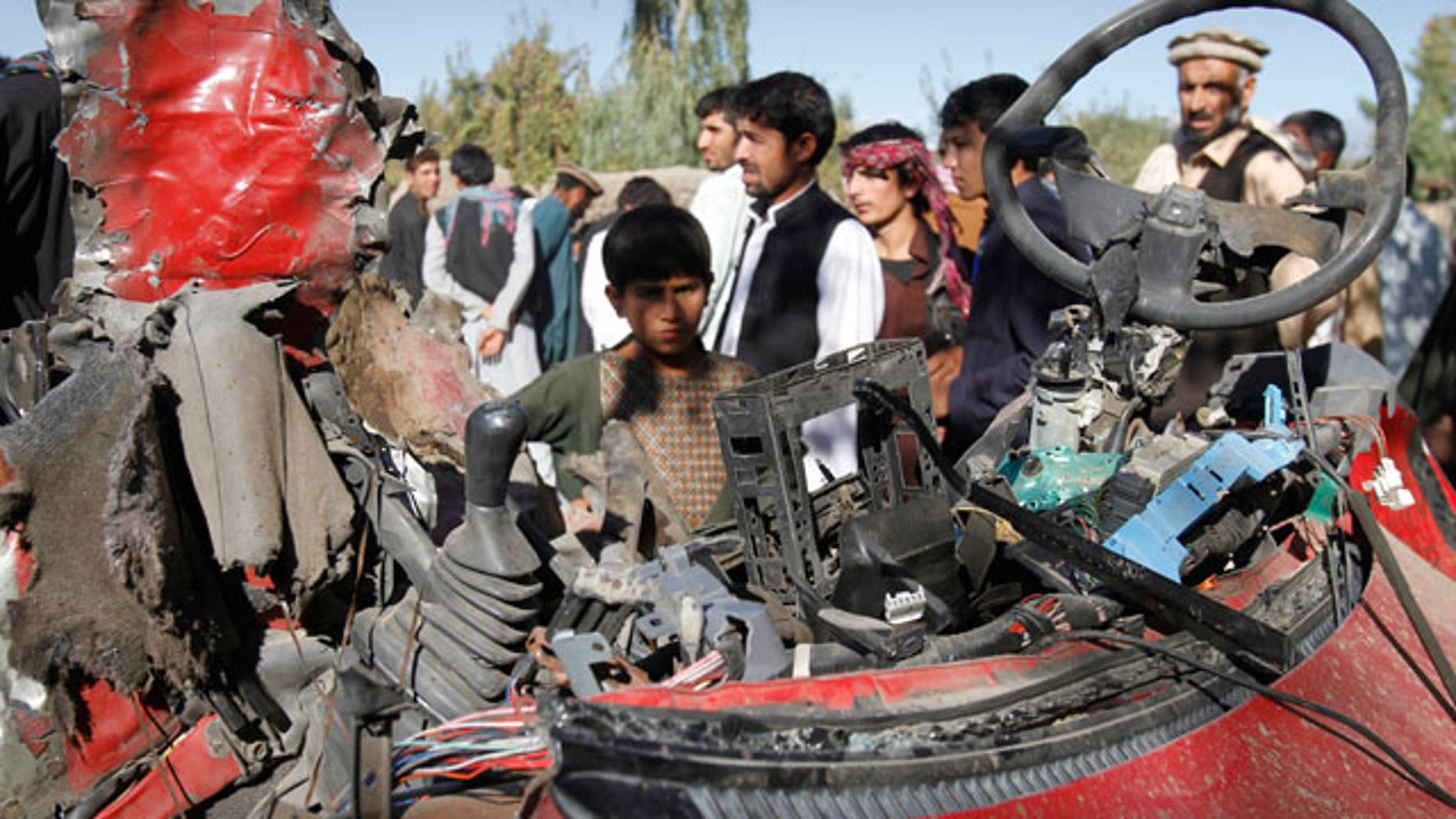 Nov. 12, 2011: Afghans stand around wreckage of a civilian car, which was hit by a roadside bomb in Laghman, east of Kabul, Afghanistan.