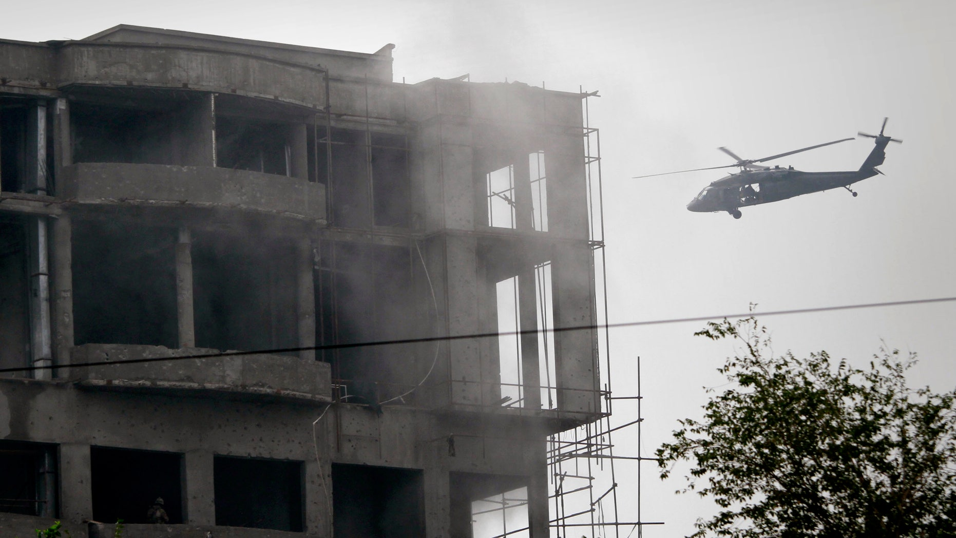 A military helicopter belonging to coalition forces flies around a building during a gun battle with Taliban militants in Kabul, Afghanistan on Wednesday Sept. 14,2011.