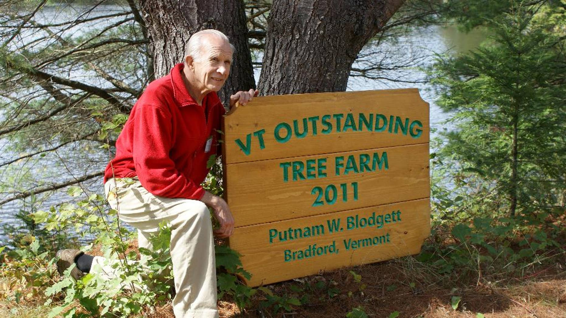 """In this 2011 photo, Putnam """"Put"""" Blodgett poses by a sign announcing he was named Vermont's 2011 Outstanding Tree Farmer in Bradford, Vt. Blodgett, president of the Vermont Woodlands Association, has implemented a succession plan for his 670 acres family owned forest land by forming a limited liability company and establishing a conservation easement on the land that prohibits development and mandates professional forest management. (AP Photo/Vermont Woodlands Association)"""