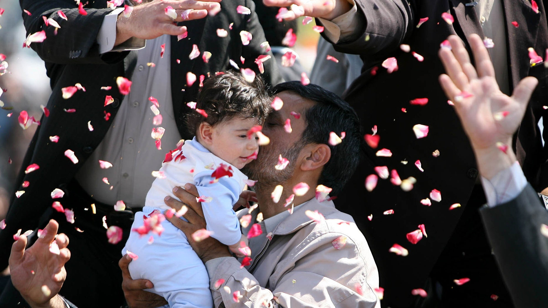 In this May, 20, 2009 photo, Iran's President Mahmoud Ahmadinejad hugs a child and is showered with flower petals during his visit to Semnan, Iran. Iranian President Mahmoud Ahmadinejad inaugurated a new policy on July 27, 2010 to encourage population growth, whereby the government will pay families for every new child. (AP)