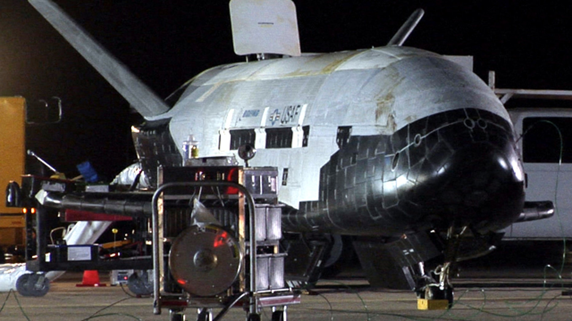 Despite its robotic nature, the X-37B space plane received a warm welcome from Air Force crews at Vandenberg. Here, the vehicle appears to be undergoing safing procedures after landing on Dec. 3 at 1:16 a.m. PST (0916 GMT). Significant weathering, or discoloration, can be seen on the spacecraft's upper thermal blanket insulation.