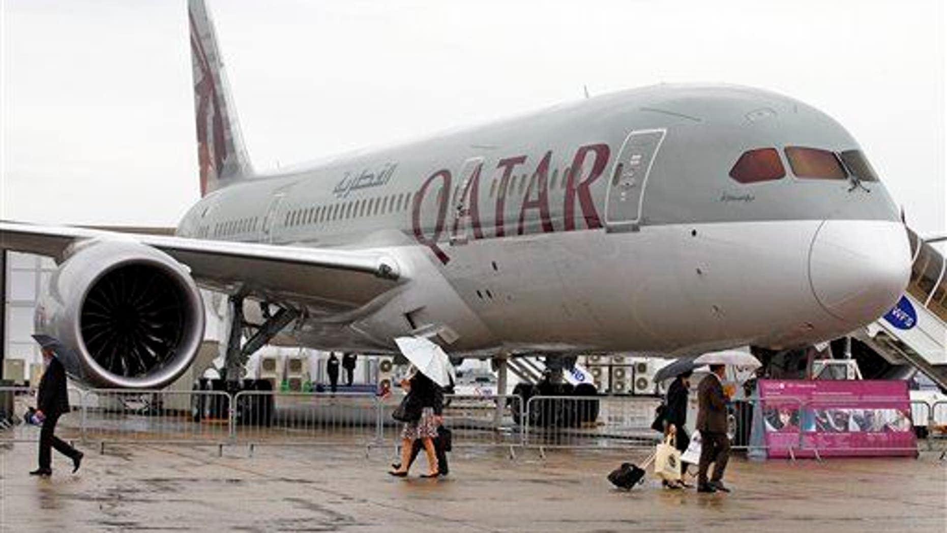 Visitors walk past a Qatar Airways Boeing Dreamliner, displayed at the 50th Paris Air Show at Paris-Le Bourget Airport, north of Paris, June 20, 2013.