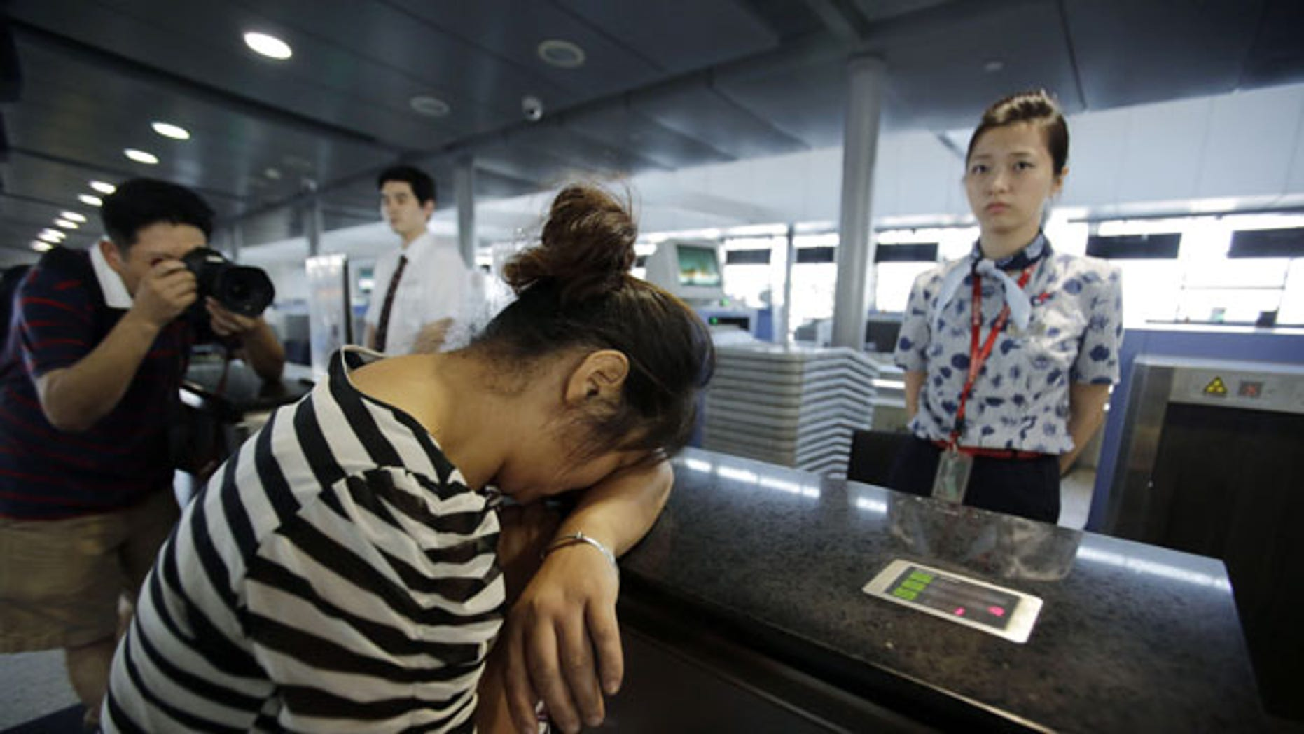 FILE - In this July 8, 2013 file photo, an unidentified family member of one of two Chinese students killed in a crash of an Asiana Airlines' plane on Saturday, cries at the airline's counter as she and other family members check in for a flight to San Francisco, at Pudong International Airport in Shanghai, China.