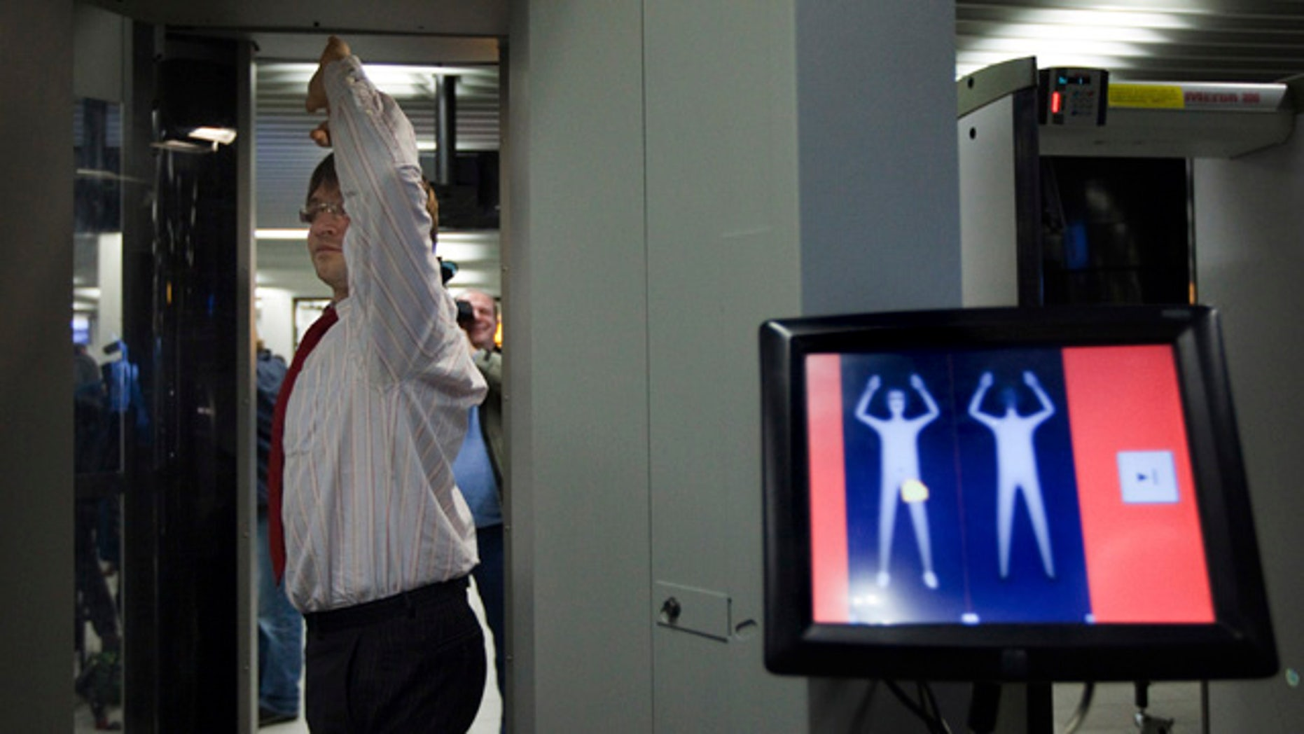 """An employee of Schiphol stands inside a body scanner during a demonstration at a press briefing at Schiphol airport, Netherlands. The Netherlands announced Wednesday, Dec. 30, it will immediately begin using full body scanners for flights heading to the United States, issuing a report that called the failed Christmas Day airline bombing a """"professional"""" terror attack."""