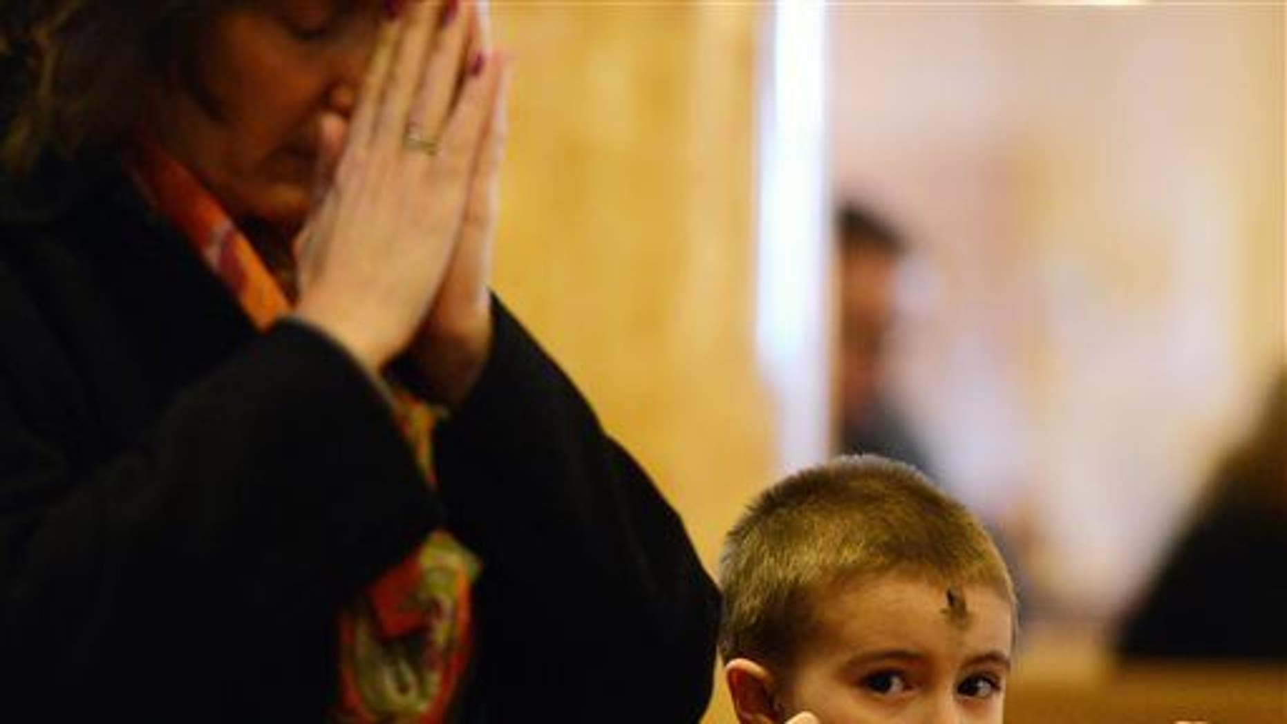 Michelle Commisso and her grandson Christian Vella, 5, attend an Ash Wednesday service at St. Mary of Mount Carmel/Blessed Sacrament Church, Wednesday, Feb. 18, 2015, in Utica, N.Y. (AP Photo/Observer-Dispatch, Mark DiOrio)  ROME OUT