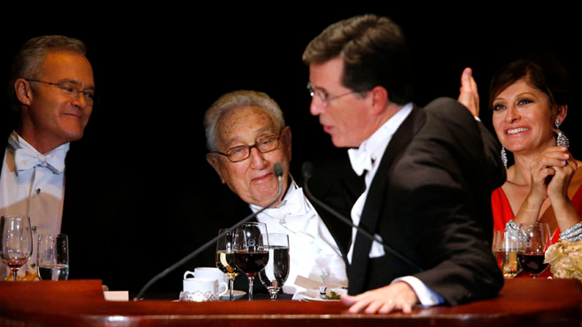 Oct. 17, 2013: Keynote speaker Stephen Colbert pokes fun at former U.S. Secretary of State Henry Kissinger, center, and CNBC anchor Maria Bartiromo, right, as CBS Evening News anchor Scott Pelley, left, looks on during the Alfred E. Smith Memorial Foundation Dinner, a charity gala organized by the Archdiocese of New York, at the Waldorf-Astoria hotel, in New York.
