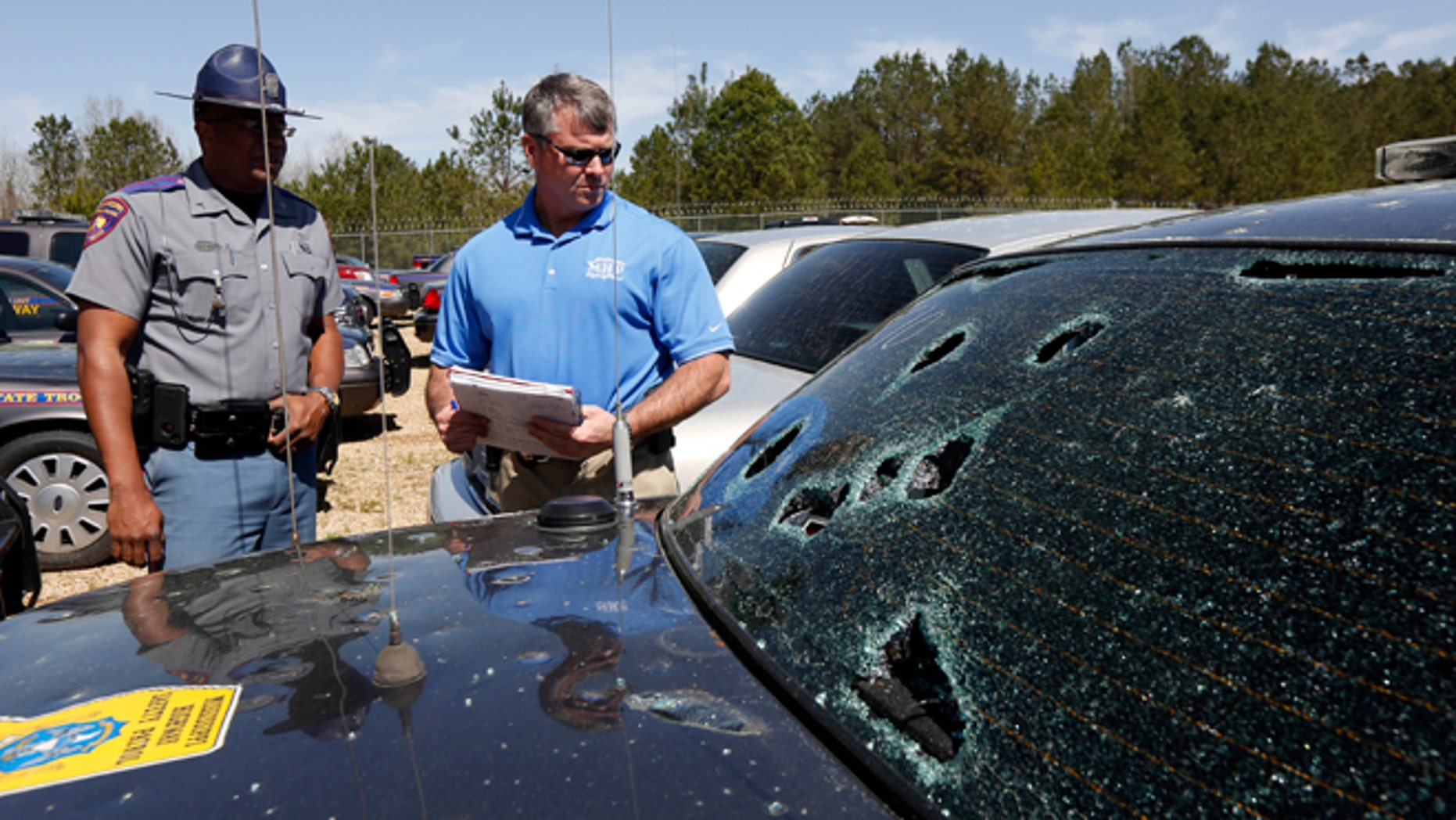 March 19: Mississippi Highway Patrol Lt. Col. Mike Holmes, right, and Cpl. Odis Easterling, survey the damage made by hail stones to a crusier in Pearl, Miss.