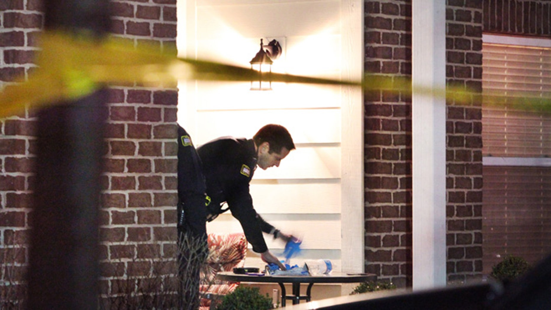 Jan. 9, 2013: A Noblesville policeman sets out crime scene gloves on a patio table, the scene of a stabbing in Noblesville, Ind.