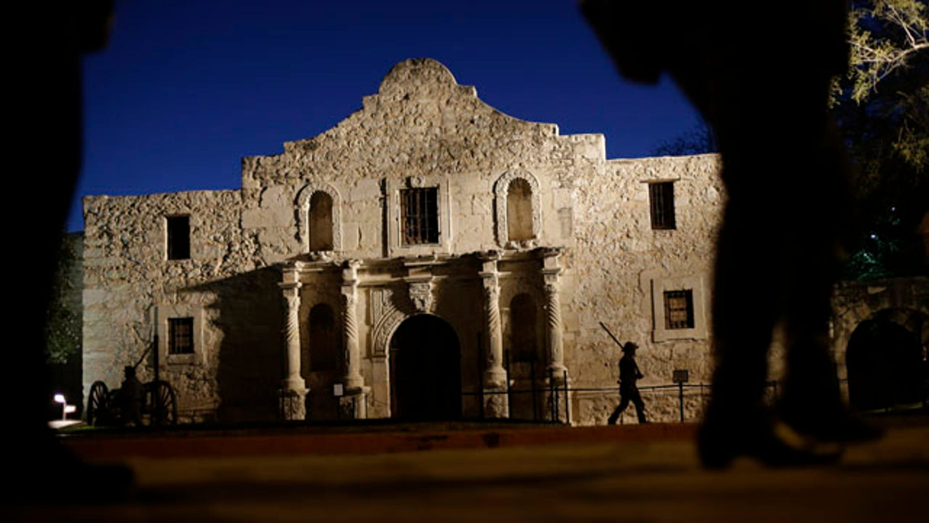 File - In this March 6, 2013, file photo, Dan Phillips, a member of the San Antonio Living History Association, patrols the Alamo during a pre-dawn memorial ceremony to remember the 1836 Battle of the Alamo and those who fell on both sides. (AP Photo/Eric Gay, File)