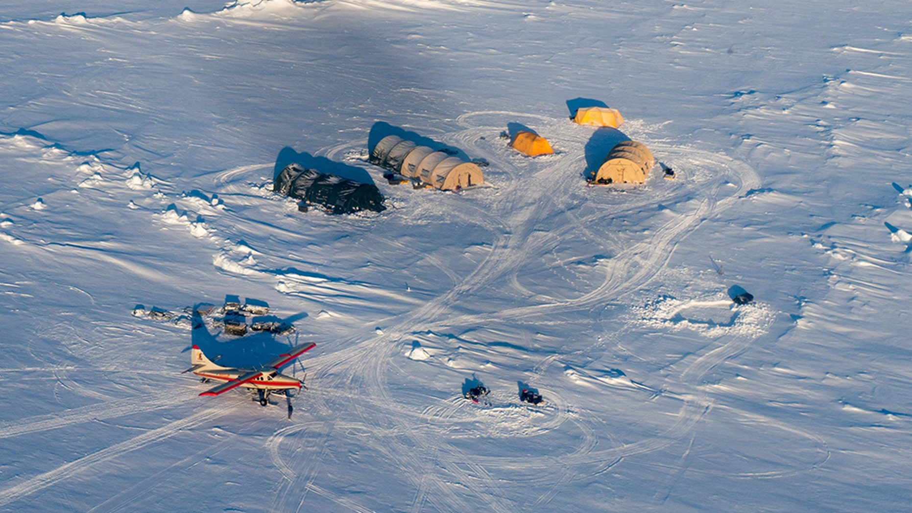 A helicopter flies over Arctic ice towards the Applied Physics Laboratory Ice Station in Alaska.