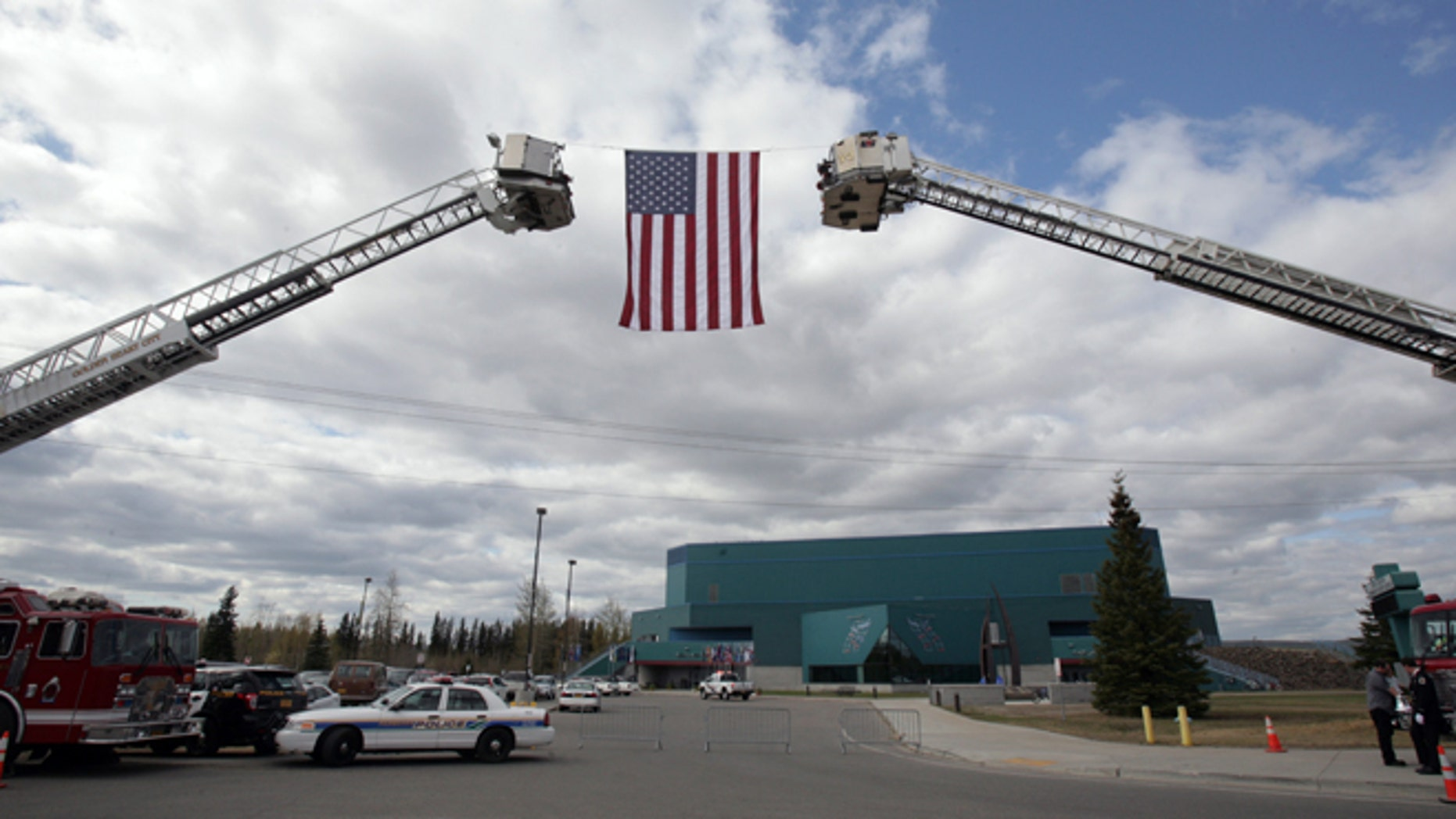 """May 10, 2014: The American Flag hangs from two fire department ladder trucks during the memorial service for Alaska State Trooper Sgt. Patrick """"Scott"""" Johnson and Trooper Gabriel """"Gabe"""" Rich at the Carlson Center in Fairbanks, Alaska."""