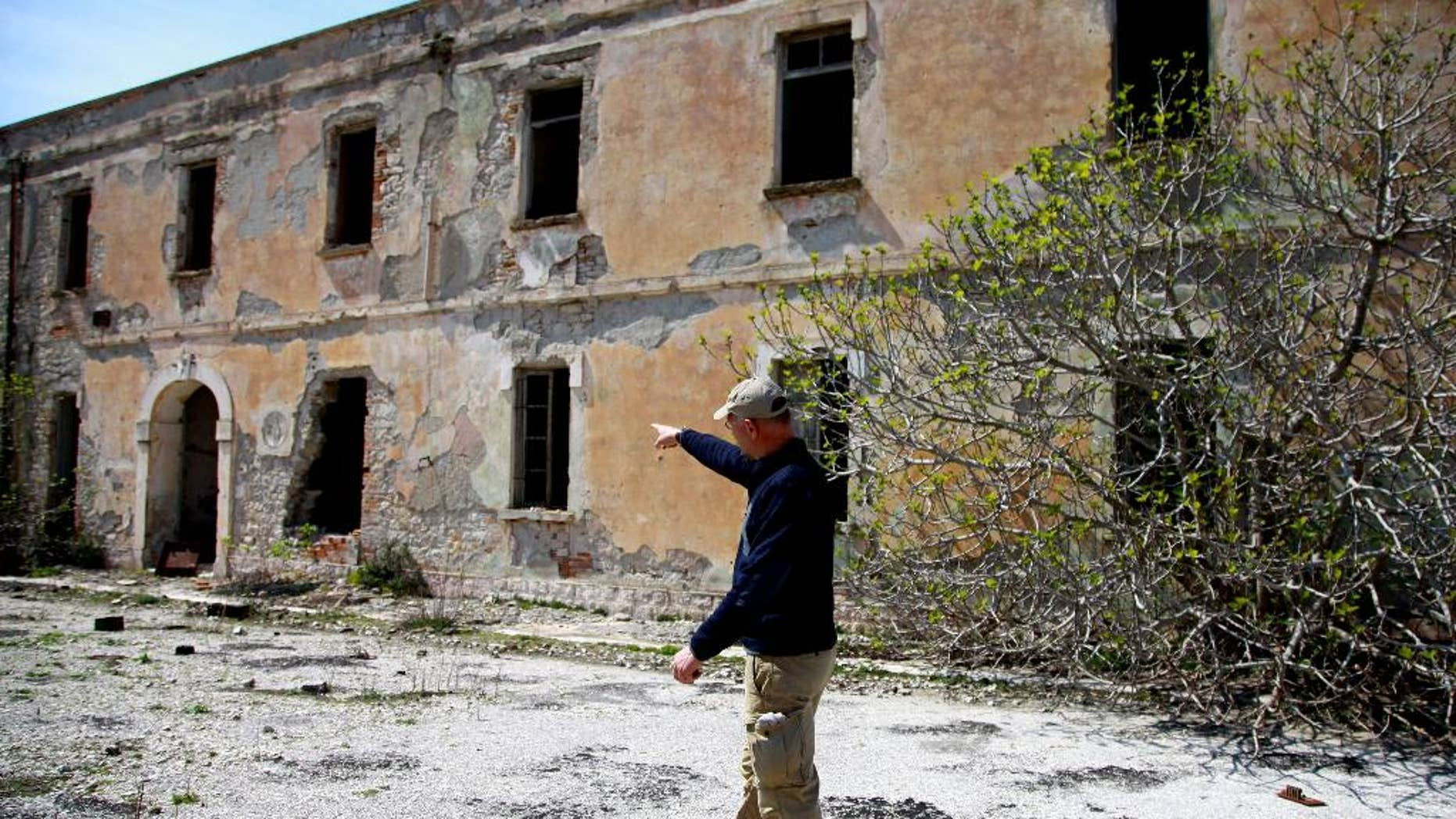 This April 14, 2015: Auron Tare of the Albanian National Coastal Agency pointing to the army command building was built by the Italians on Sazan Island, 85 miles southwest of Albania's capital Tirana.