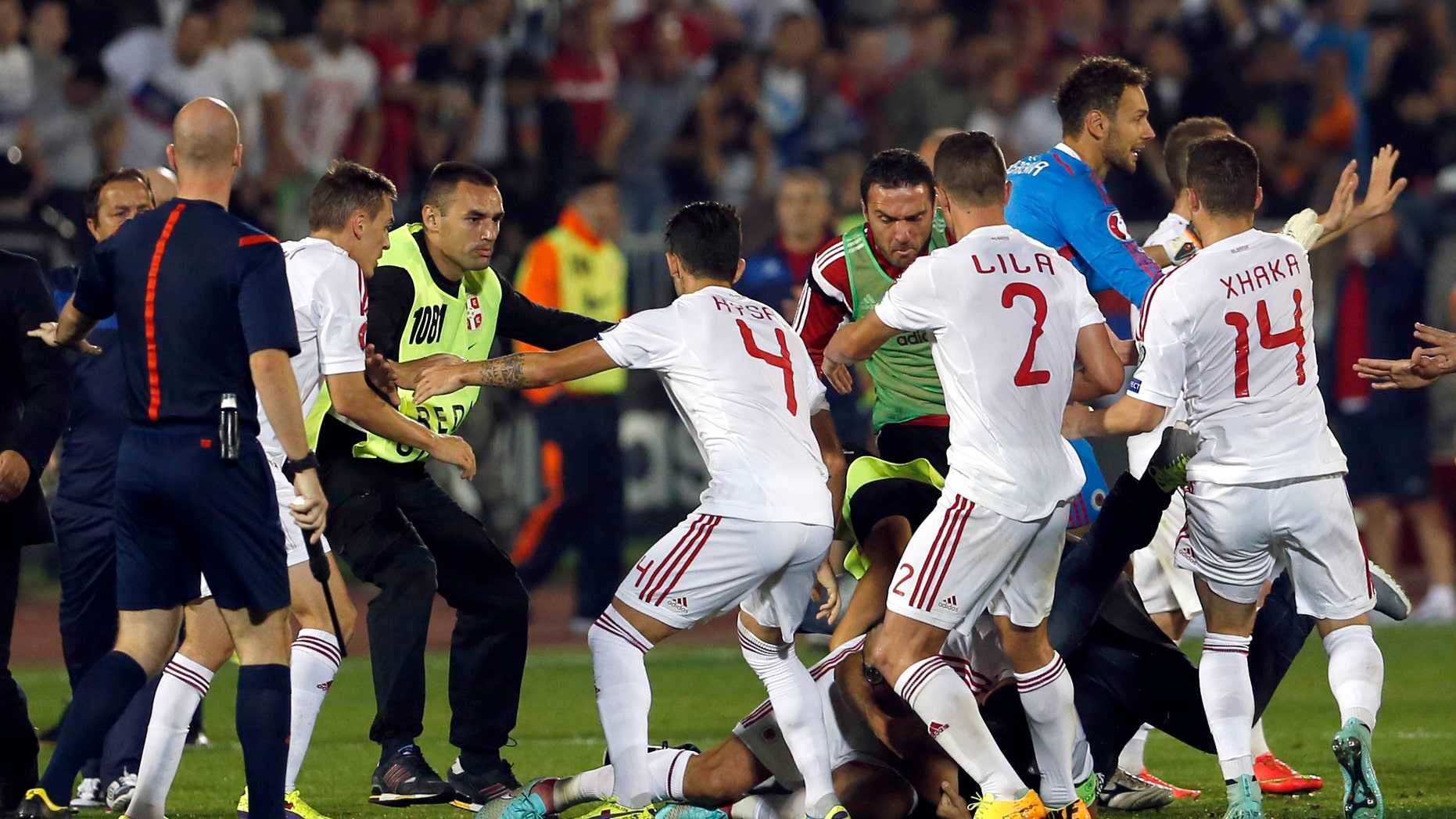 A skirmish between Serbian and Albanian players breaks out on the pitch during the Euro 2016 Group I qualifying match between Serbia and Albania in Belgrade, Serbia, Tuesday, Oct. 14, 2014. The European Championship qualifier between Serbia and Albania was suspended on Tuesday after pitch skirmishes involving players and fans over an Albanian flag that was flown above the stadium by a drone. (AP Photo/Marko Drobnjakovic)