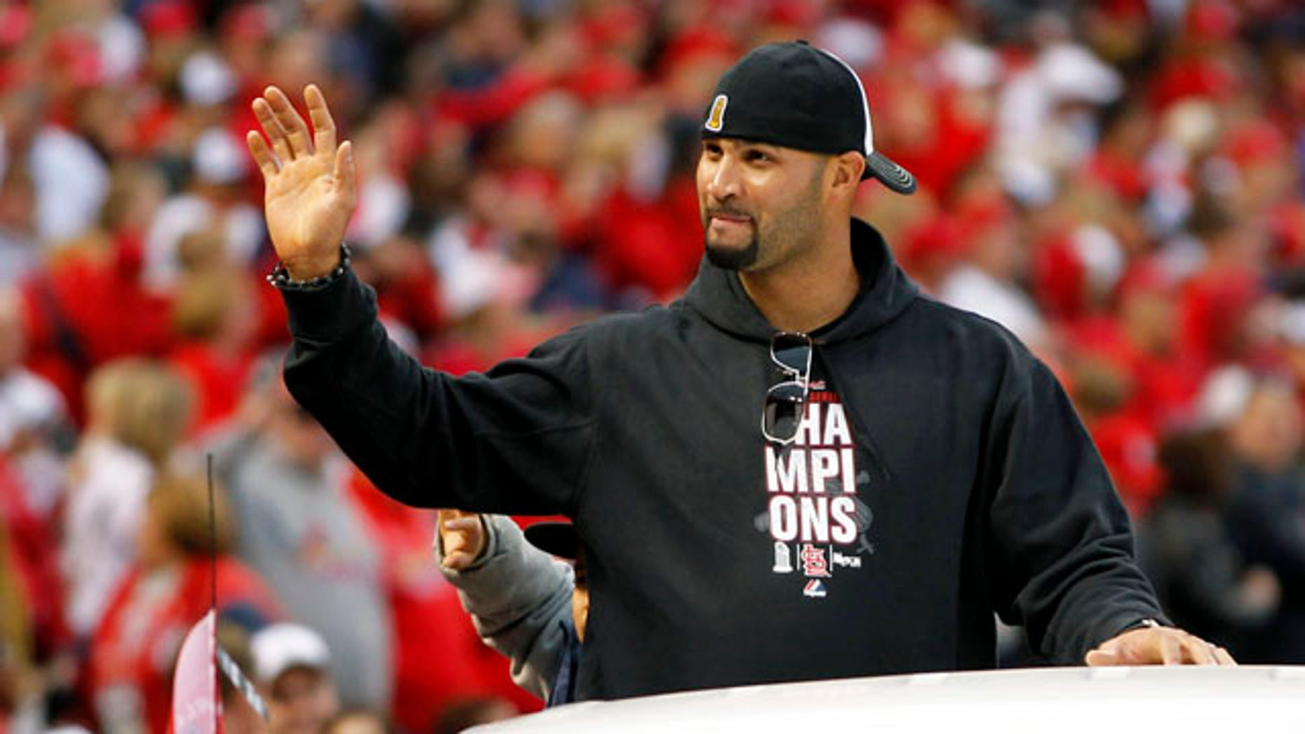 St. Louis Cardinals' Albert Pujols waves to fans at Busch Stadium during a victory parade in celebration of the Cardinals' 11th World Series victory, Sunday, Oct. 30, 2011, in St. Louis. The free agent has reportedly been wooed by the Cardinals and the Marlins. (AP Photo/Jeff Roberson)