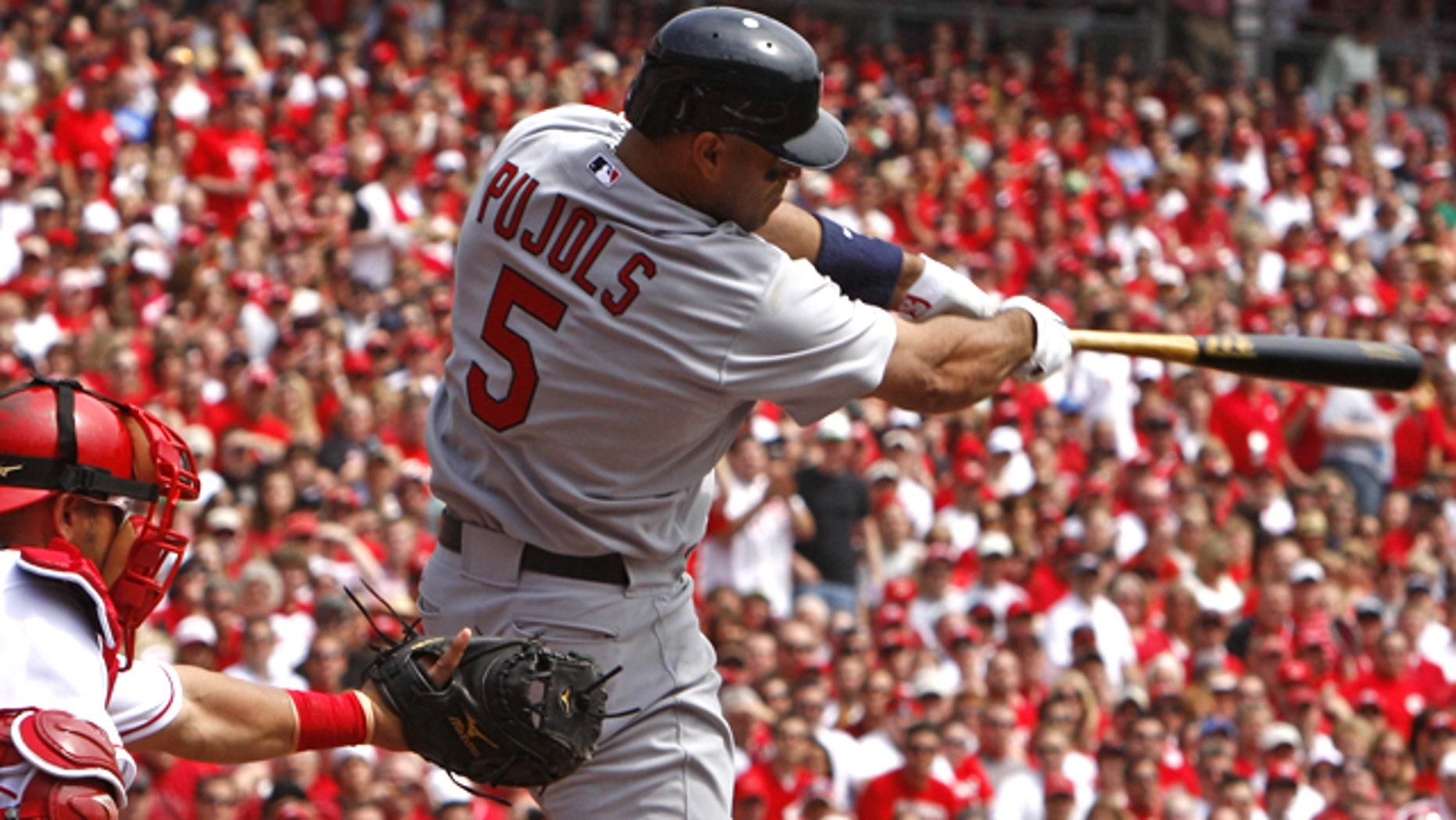 St. Louis Cardinals' Albert Pujols hits a solo home run off Cincinnati Reds pitcher Aaron Harang in the first inning of a baseball game, Monday, April 5, 2010, in Cincinnati. Cincinnati Reds' Ramon Hernandez catches at left.