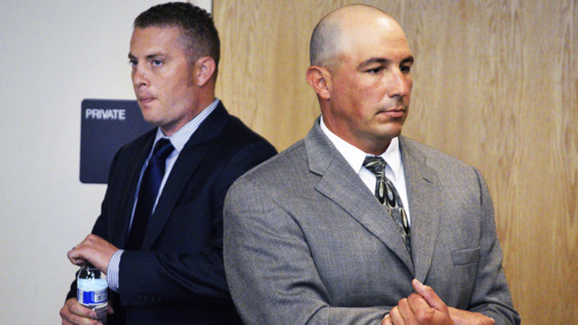 FILE - In a Monday, Aug. 3, 2015 file photo, Albuquerque officer Dominique Perez, left, and former Albuquerque Detective Keith Sandy, right, stand up in court at a preliminary hearing in  Albuquerque, N.M. Pro Tem Judge Neil Candelaria is scheduled Monday, Aug. 17, 2015, to hear more testimony in a preliminary hearing for Perez and Sandy. They are facing murder charges for the death of James Boyd, who was shot during a standoff in March 2014 in the Sandia Mountains foothills.  (AP Photo/Russell Contreras, File)