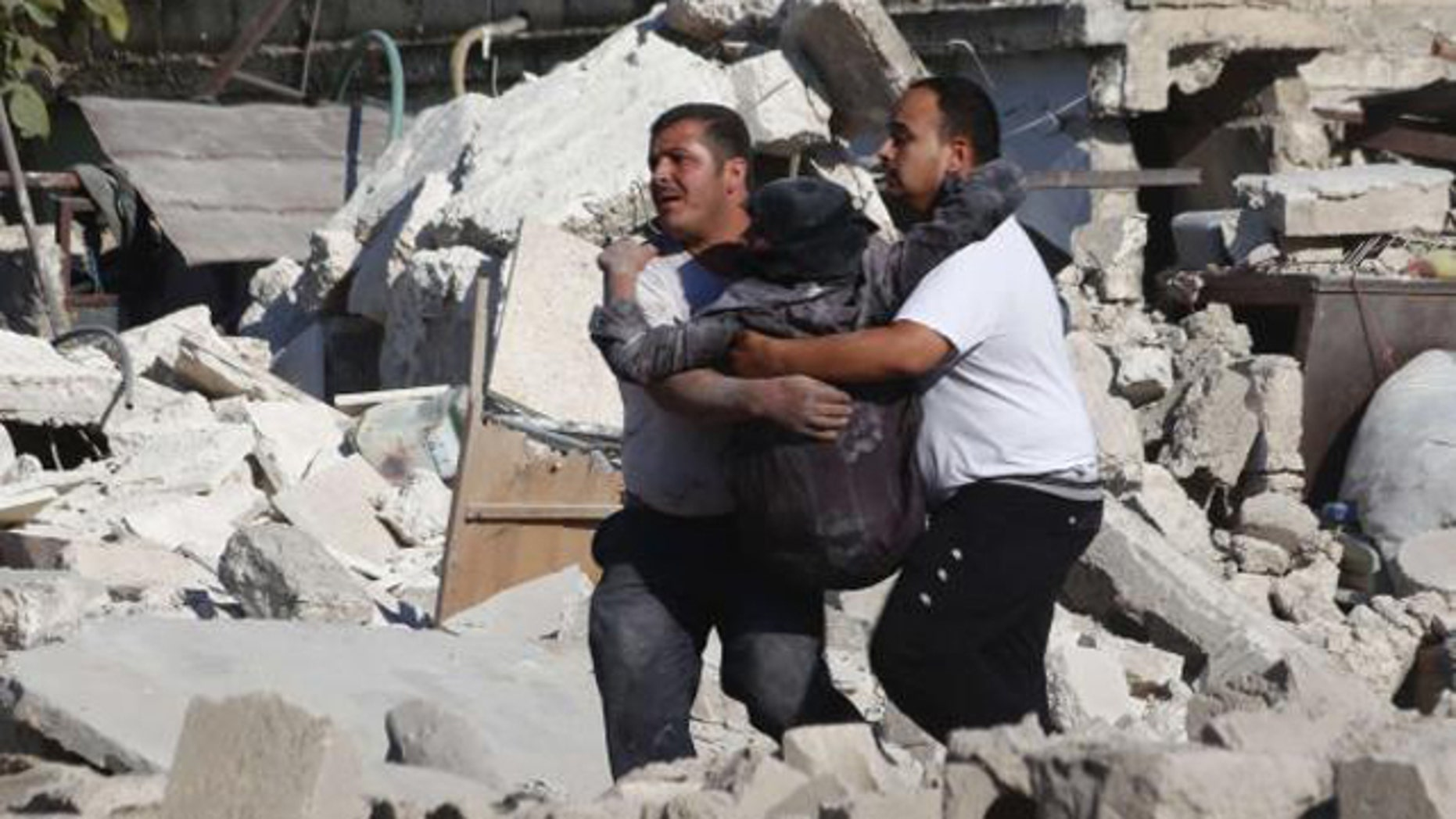 August 11, 2014: Men carry a wounded woman at a site hit by what activists said was a missile fired by forces loyal to Syria's President Bashar al-Assad at Aleppo's Bab al-Nairab district. (REUTERS/Rami Zayat)