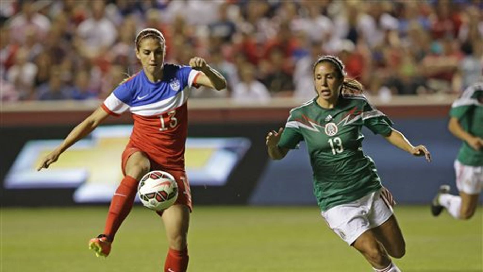 United States' forward Alex Morgan (13) scores as Mexico'a Bianca Sierra (13) defends in the first half of an international friendly game at Rio Tinto Stadium, Saturday, Sept. 13, 2014, in Sandy, Utah. (AP Photo/Rick Bowmer)