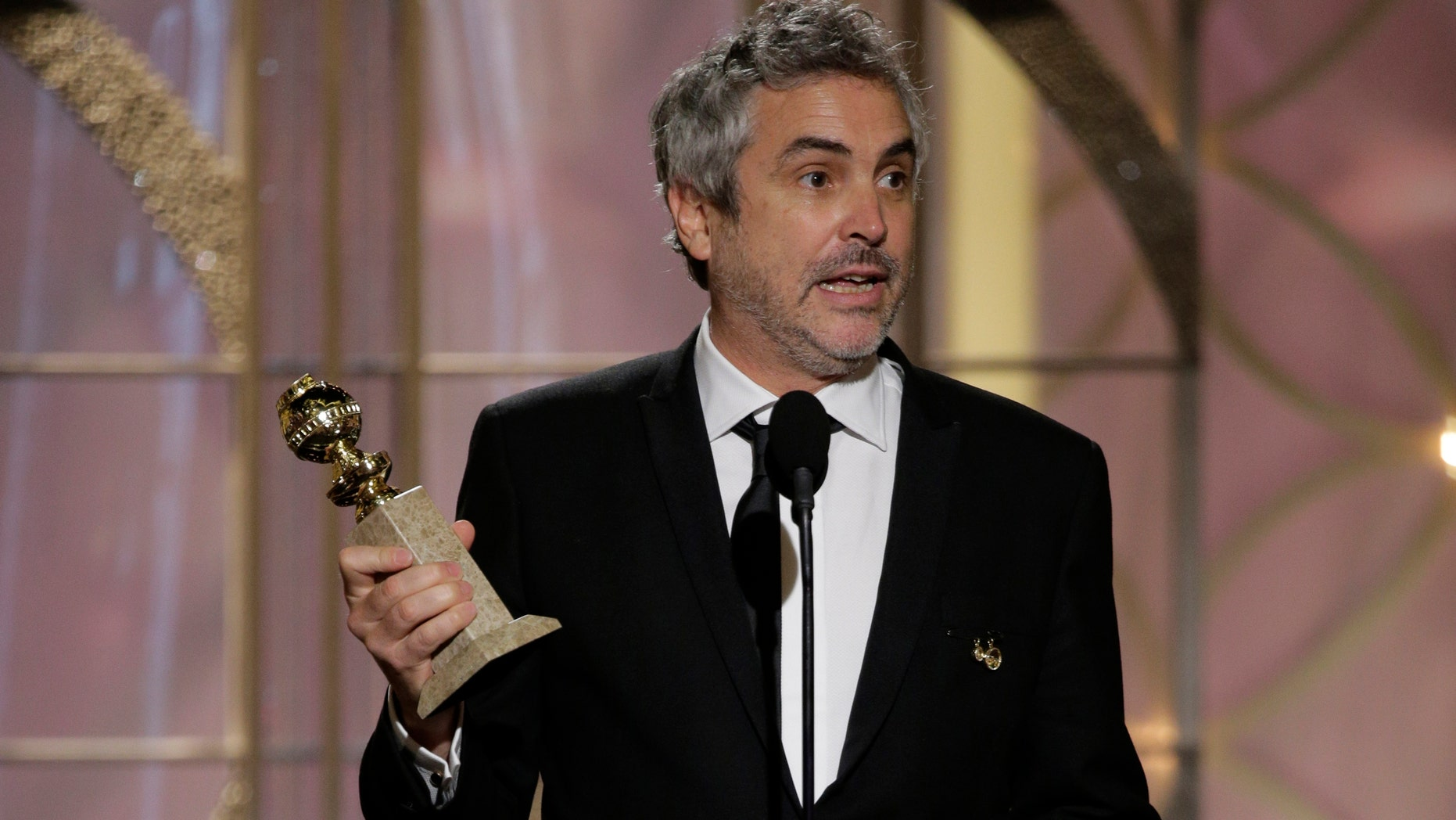 """BEVERLY HILLS, CA - JANUARY 12:  In this handout photo provided by NBCUniversal, Alfonso Cuaron accepts the award for Best Director - Motion Picture for """"Gravity"""" during the 71st Annual Golden Globe Award at The Beverly Hilton Hotel on January 12, 2014 in Beverly Hills, California.  (Photo by Paul Drinkwater/NBCUniversal via Getty Images)"""