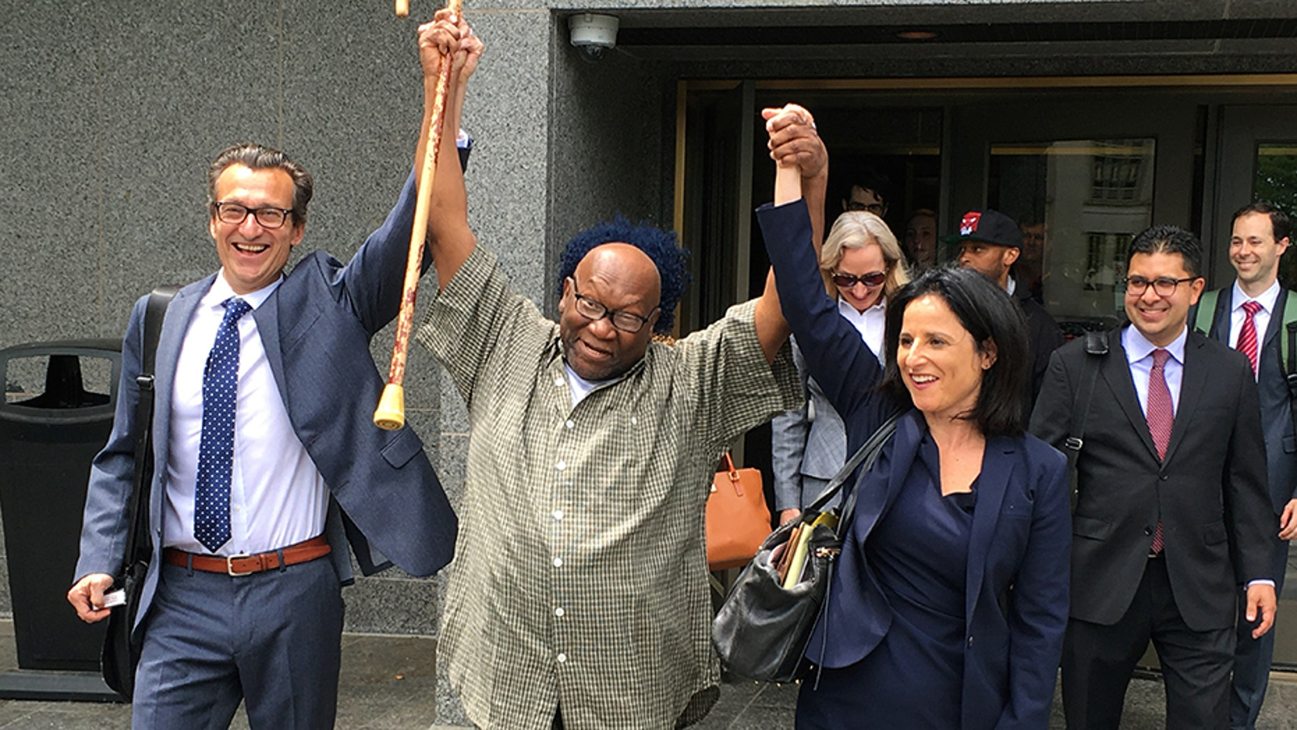Alfred Swinton and his lawyers walk out of Superior Court in Hartford, Conn., Thursday, June 8, 2017, after a judge dismissed his murder conviction in a 1991 killing. Swinton was released and will be under house arrest while the murder charge remains pending. New DNA testing showed he wasn't the source of bite marks on the victim's body. (AP Photo/Dave Collins)