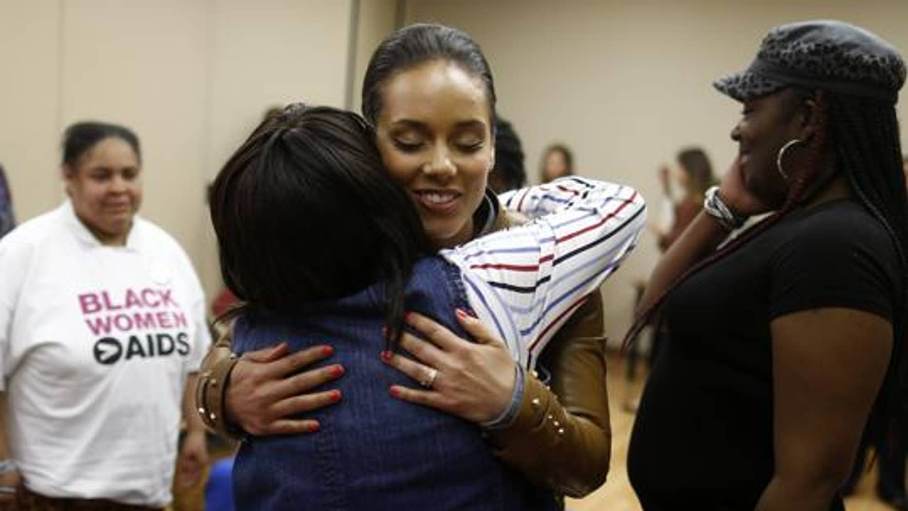 Grammy Award-winning singer Alicia Keys hugs HIV positive woman as she visits an HIV women's support group at United Medical Center in Washington, Monday, April 15, 2013.  (AP Photo/Charles Dharapak)
