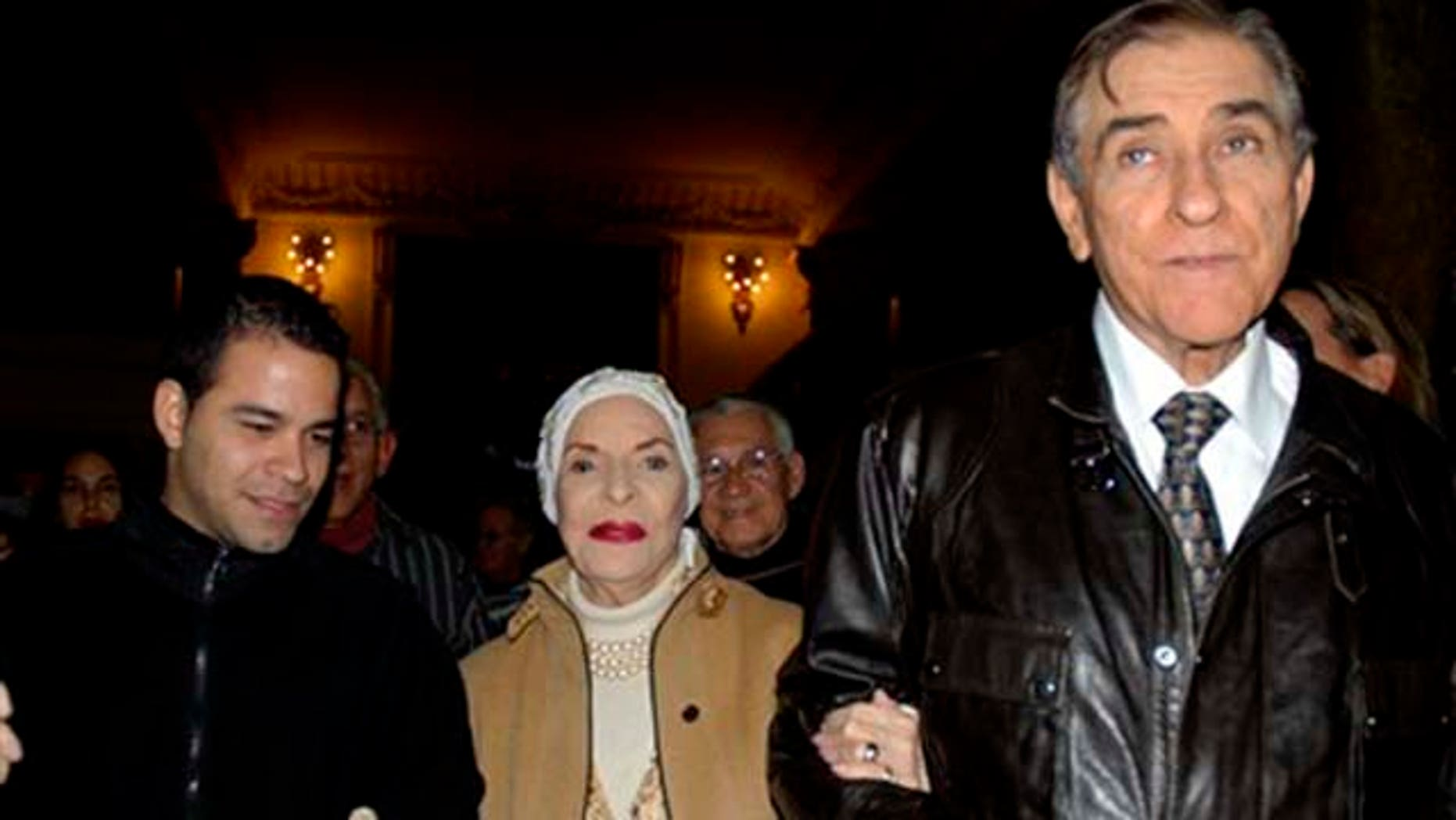 Cuban dance legend Alicia Alonso, center, is accompanied by her husband Fernando Alonso, right, as they leave a gala honoring the prima ballerina on the eve of her 90th birthday, in Havana, Cuba, Monday Dec. 20, 2010. Alonso is considered a living legend of international ballet and a national treasure in her native Cuba.  (AP Photo)