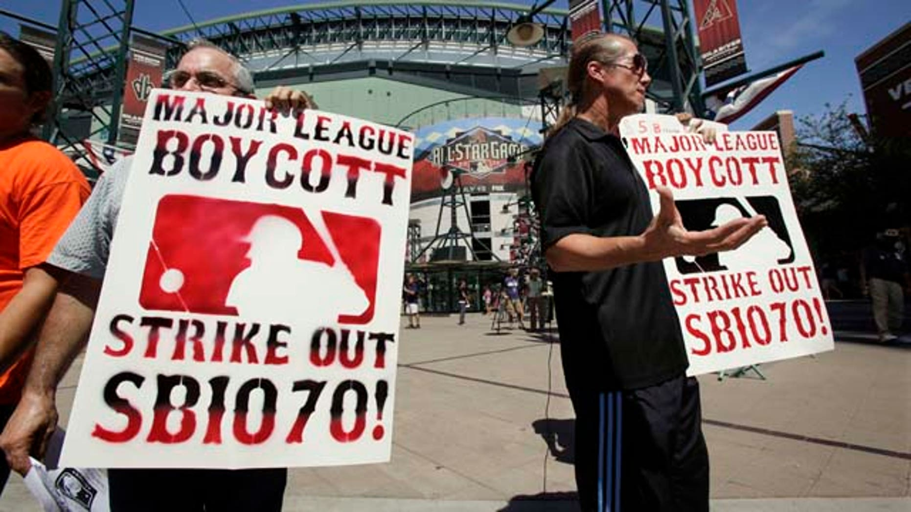 Raul Cordero, left, and Jorge Mandez protest Arizona's immigration law SB1070 outside of Chase Field before the Home Run Derby for the MLB All-Star baseball game Monday, July 11, 2011, in Phoenix. (AP Photo/Matt York)