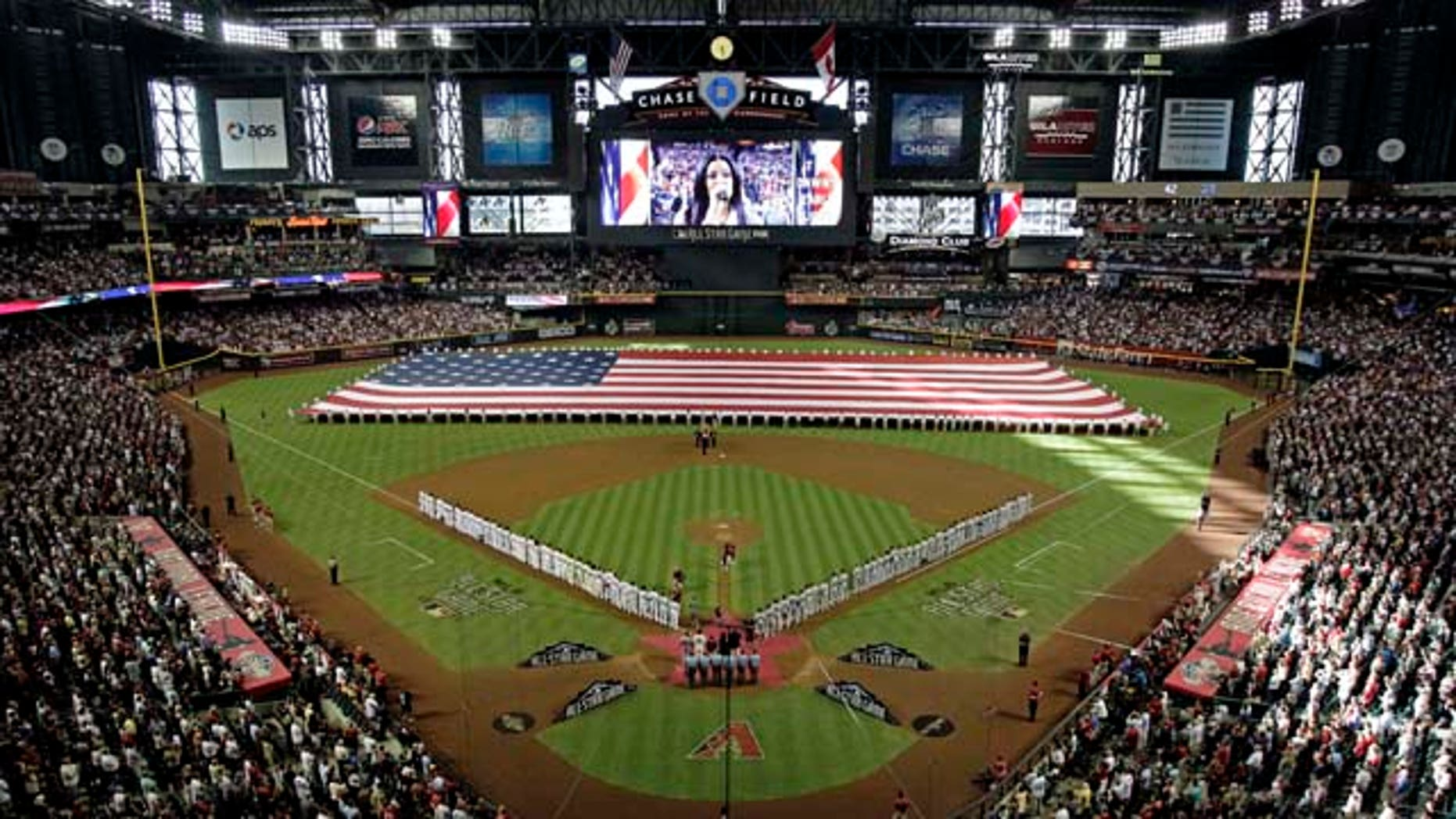 National and American League teams line the field as Jordin Sparks sings the national anthem before the MLB All-Star baseball game Tuesday, July 12, 2011, in Phoenix. (AP Photo/Matt York)