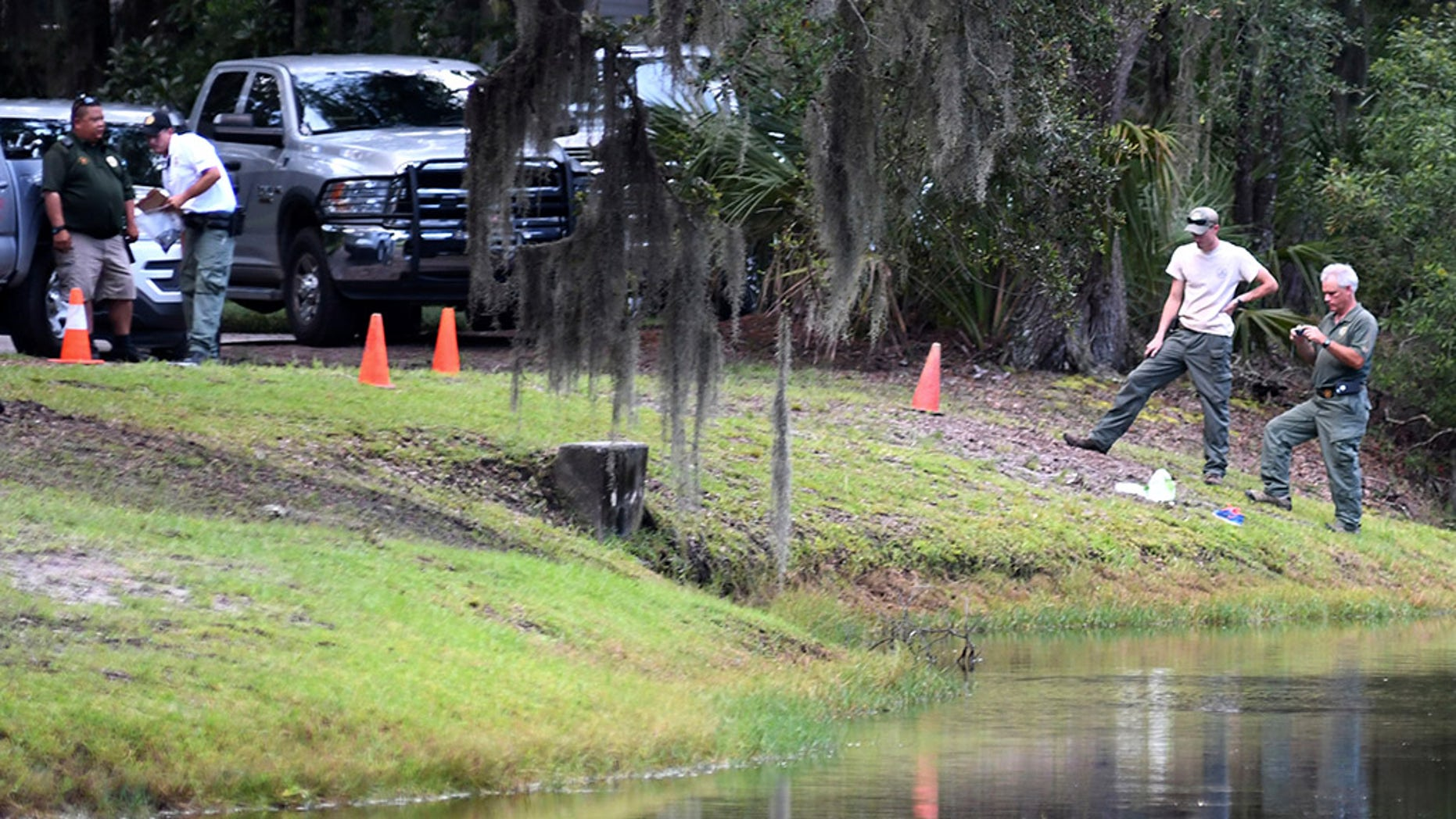 Law enforcement with S.C. Department of Natural Resources take pictures of the site where authorities say Cassandra Cline was dragged into a lagoon by an alligator and killed while trying to save her dog on Monday, Aug. 20, 2018, on Hilton Head Island, S.C. Cline was walking the dog along a residential area of Sea Pines Resort when she was attacked, state and local officials said. (Drew Martin/The Island Packet via AP)