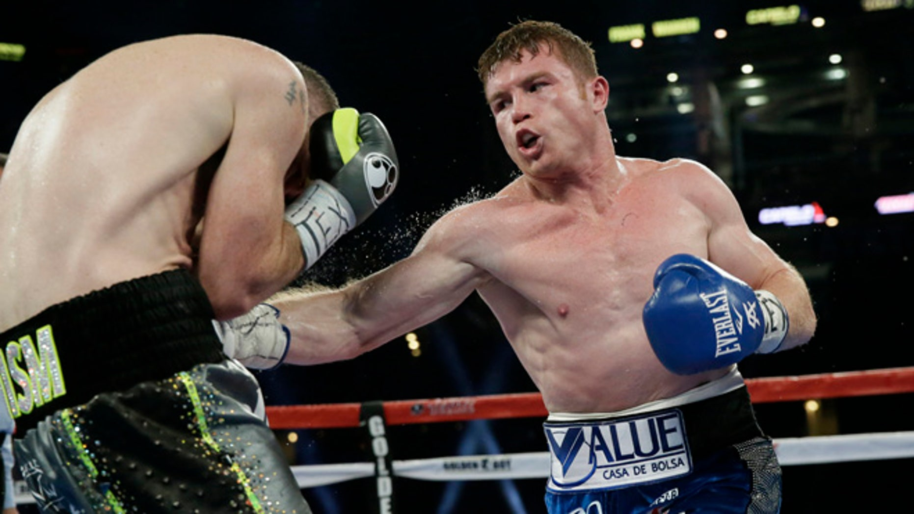 Canelo Alvarez, right, punches Liam Smith, left, during the fifth round of the WBO Junior Middleweight championship boxing match at the stadium in Arlington, Texas, Saturday, Sept. 17, 2016. Alvarez won by a knock out in the ninth round. (AP Photo/LM Otero)