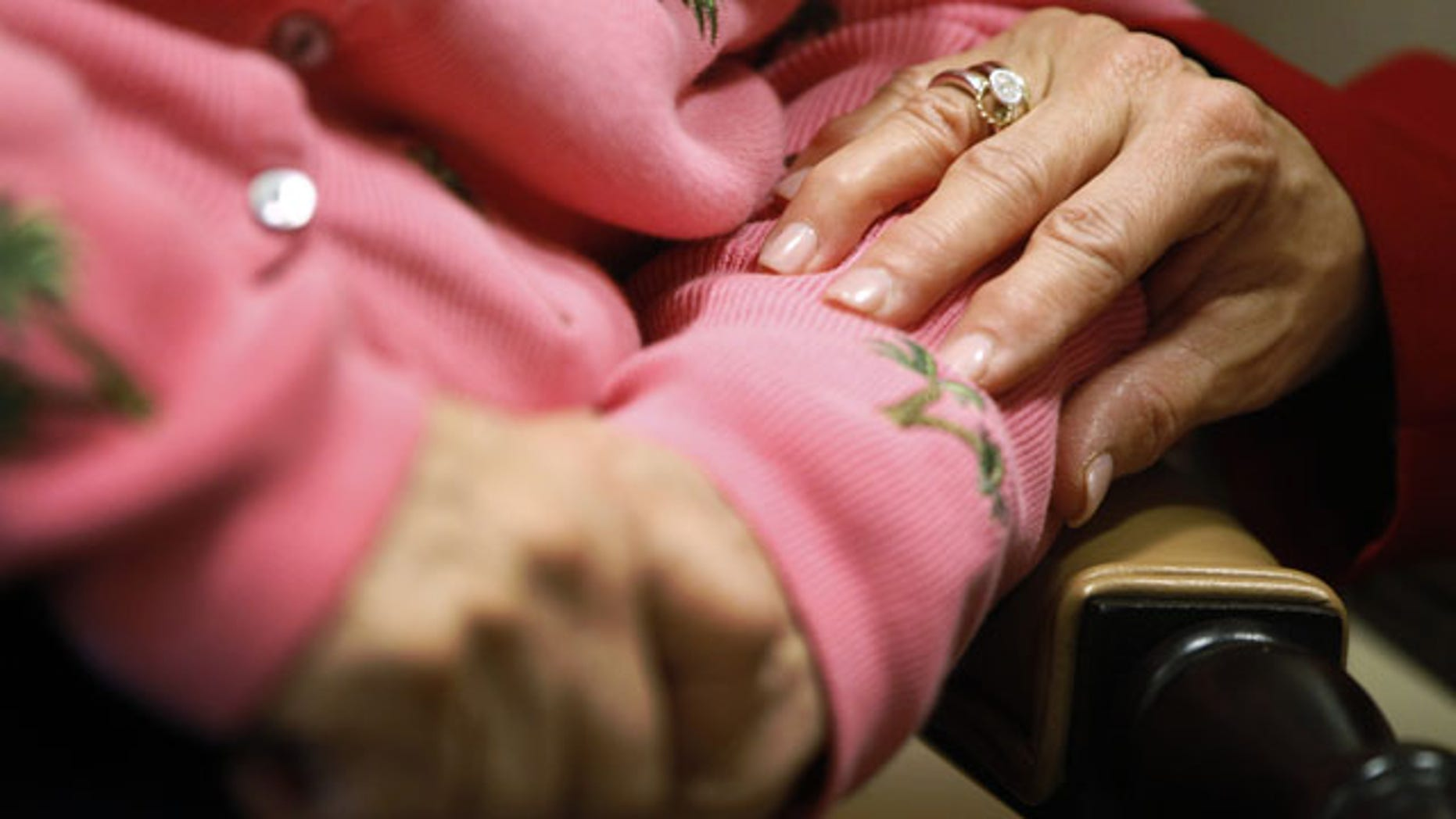 FILE - In this Feb. 6, 2012, file photo, Alexis McKenzie, right, executive director of The Methodist Home of the District of Columbia Forest Side, an Alzheimer's assisted-living facility in Washington, puts her hand on the arm of a resident. (AP Photo)