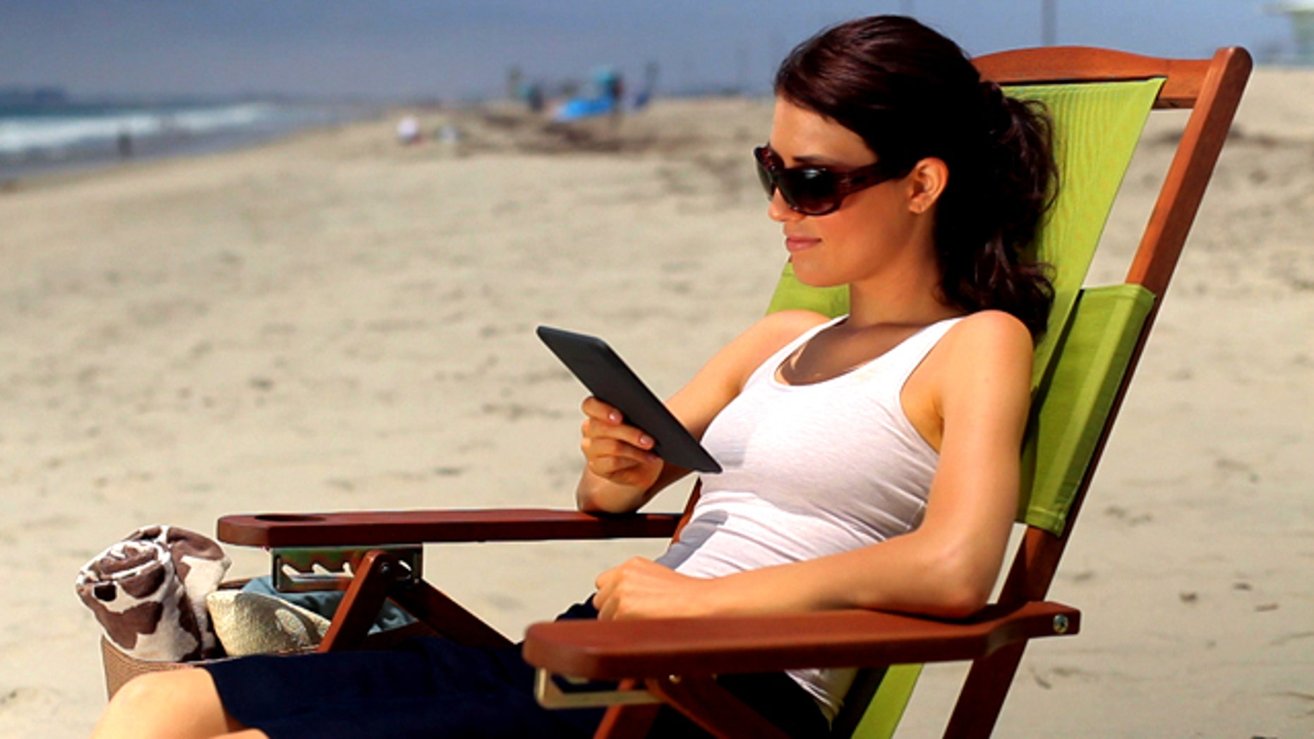A woman reads an Amazon Kindle ebook reader at the beach. The Internet retail giant is widely expected to be planning a larger tablet PC to compete with the iPad..