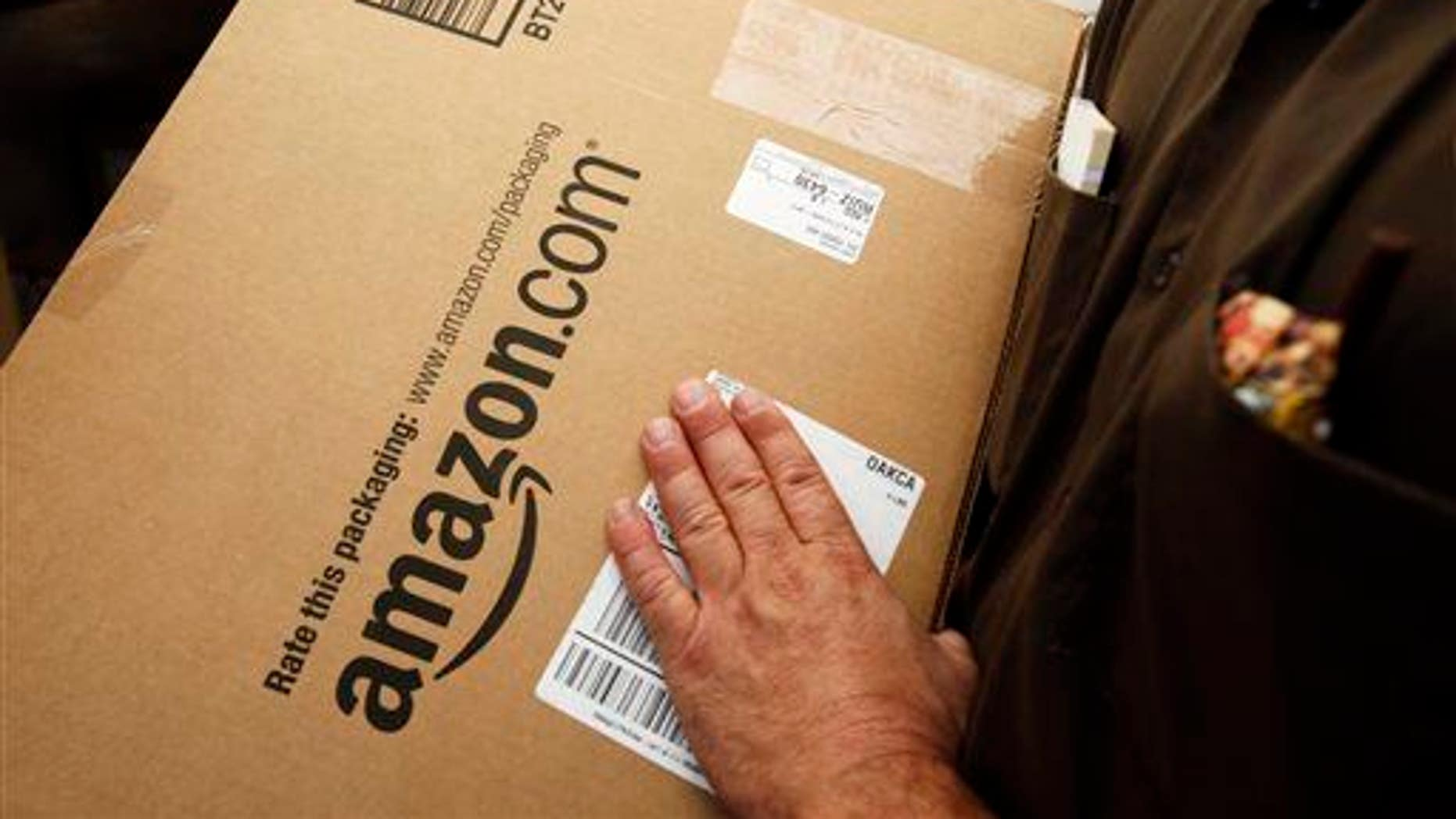 In this Oct. 18, 2010 file photo, an Amazon.com package is prepared for shipment by a United Parcel Service driver in Palo Alto, Calif.