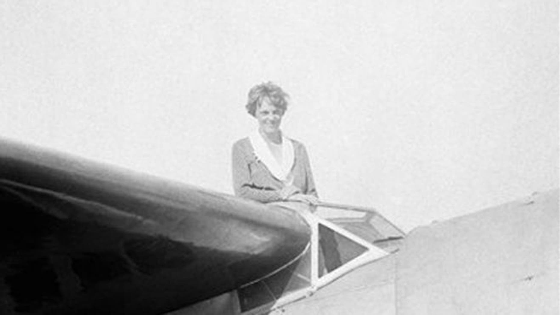 FILE: In this undated photo, Amelia Earhart, the first woman to cross the Atlantic Ocean by plane sits on top of a plane.