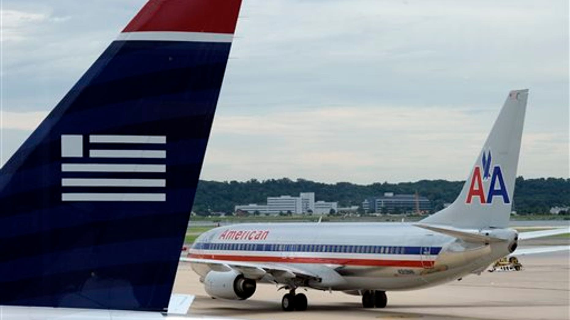 FILE - In this  Tuesday, Aug. 13, 2013, file photo, an American Airlines plane and a US Airways plane are parked at Ronald Reagan National Airport in Washington. A Federal bankruptcy judge is approving the settlement in the U.S. government's antitrust lawsuit against American Airlines and US Airways, clearing the airlines to complete their merger early December 2013. (AP Photo/Susan Walsh, File)