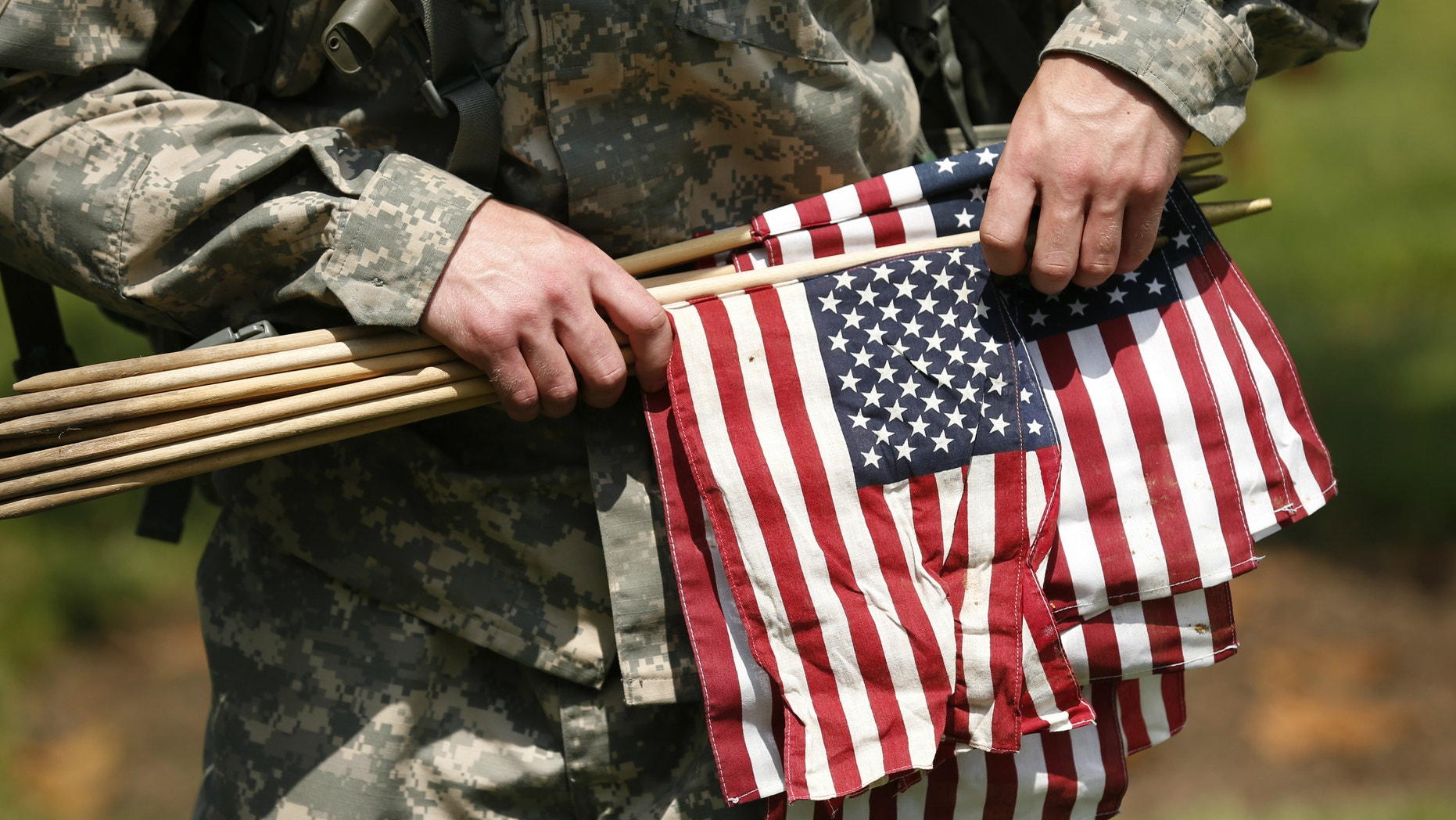 """A member of the Third U.S. Infantry Regiment (The Old Guard) carries flags during a """"Flags-In"""" ceremony at Arlington National Cemetery in Washington."""